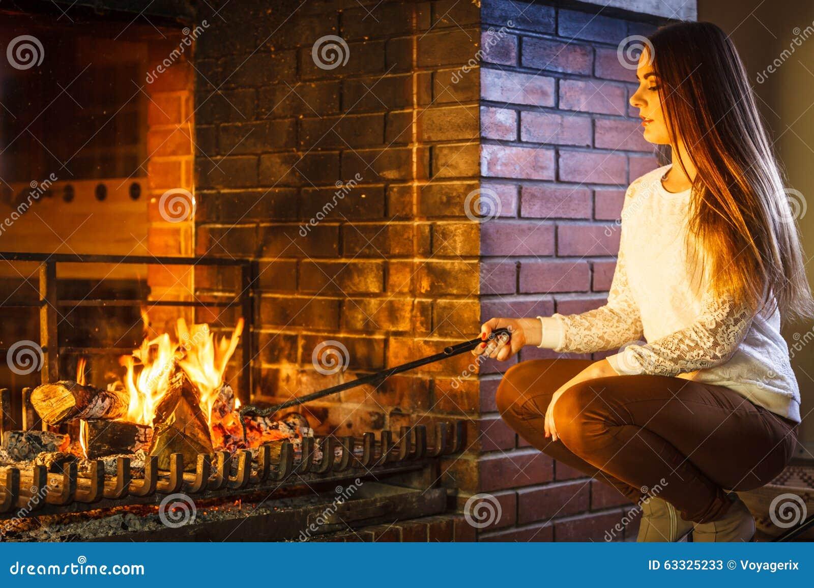 Vrouw met de pook thuis open haard van het brandijzer stock foto afbeelding 63325233 - Haard thuis wereld ...