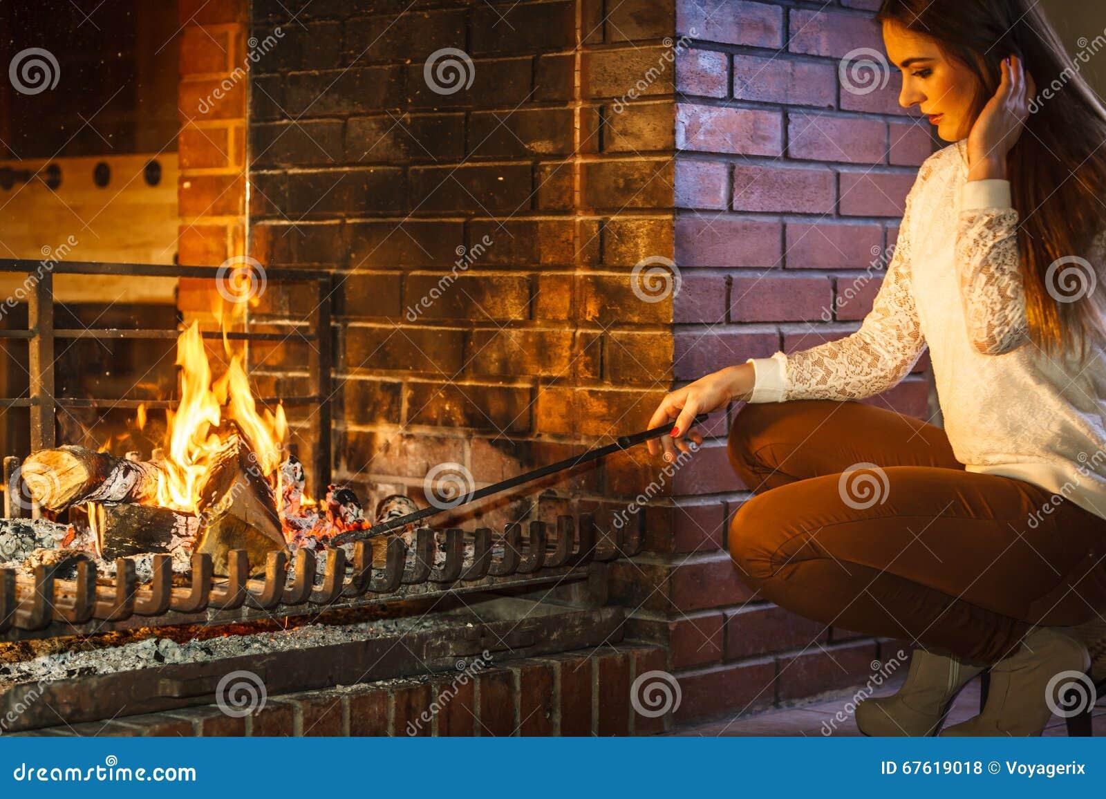 Vrouw met de pook thuis open haard van het brandijzer stock foto afbeelding 67619018 - Haard thuis wereld ...