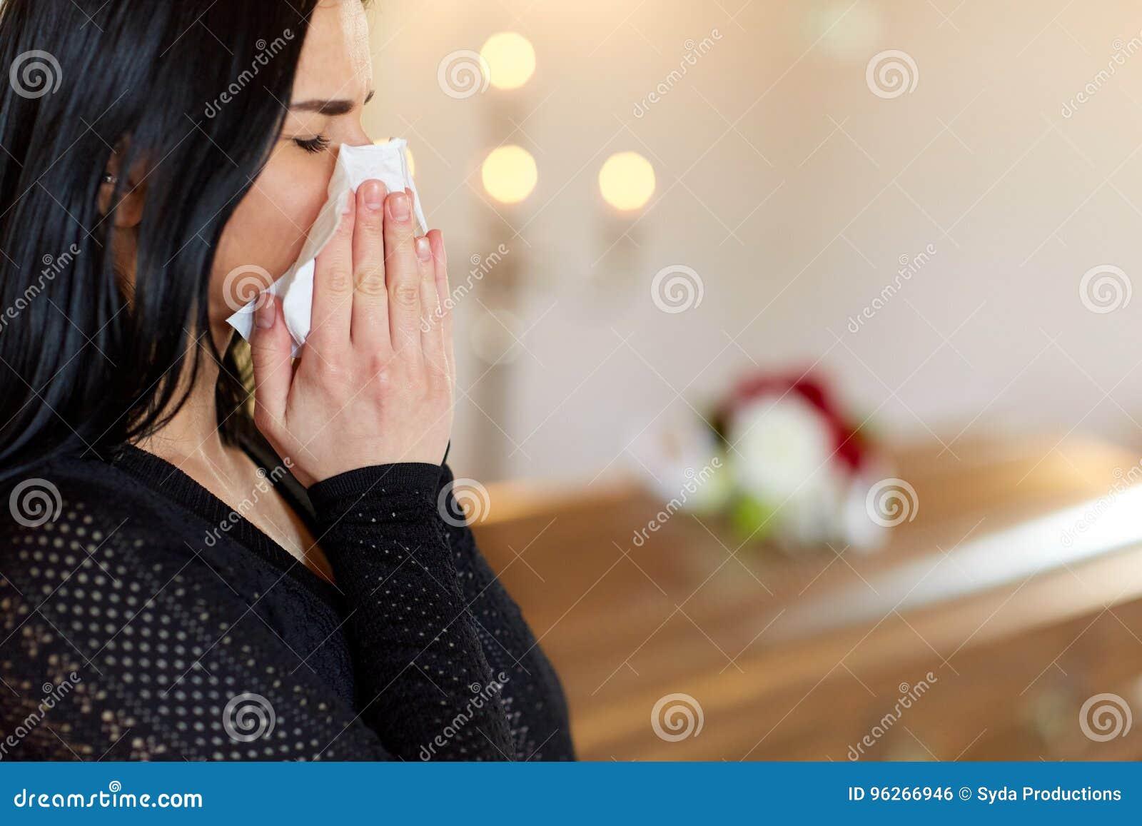 Vrouw met doodskist die bij begrafenis in kerk schreeuwen