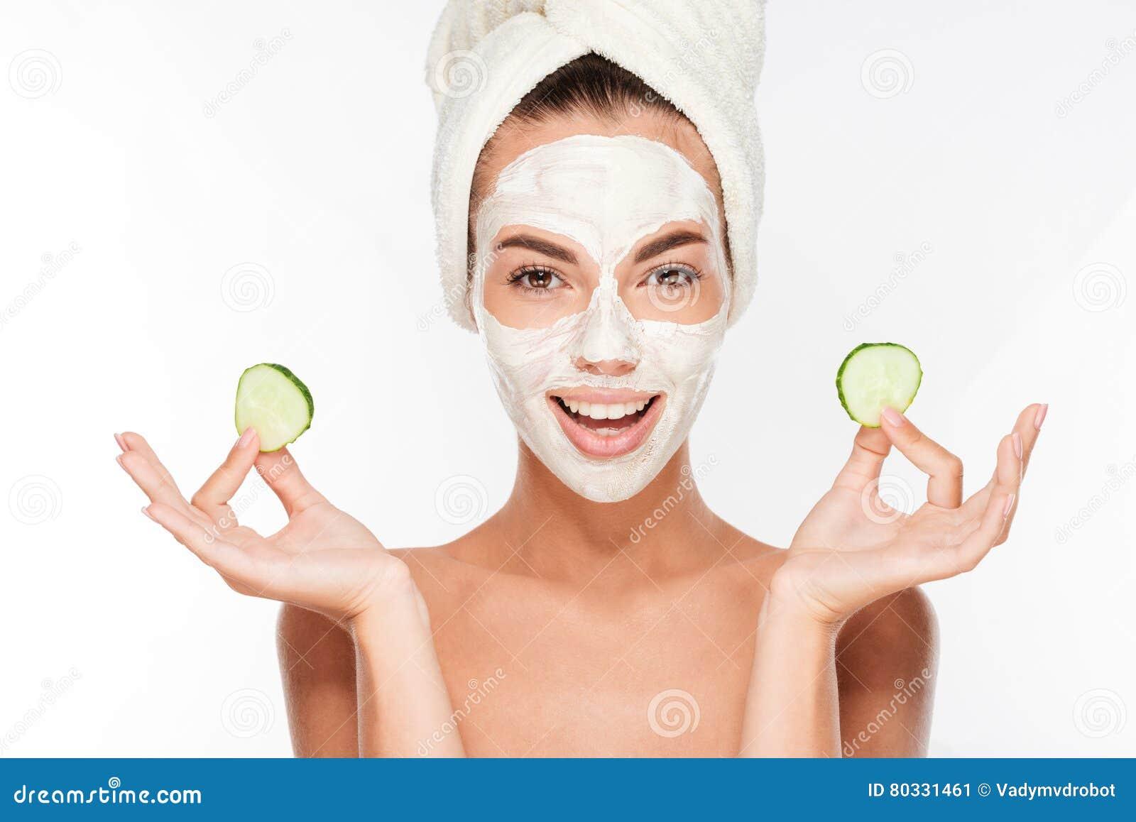 Vrouw met gezichtsmasker en komkommerplakken in haar handen