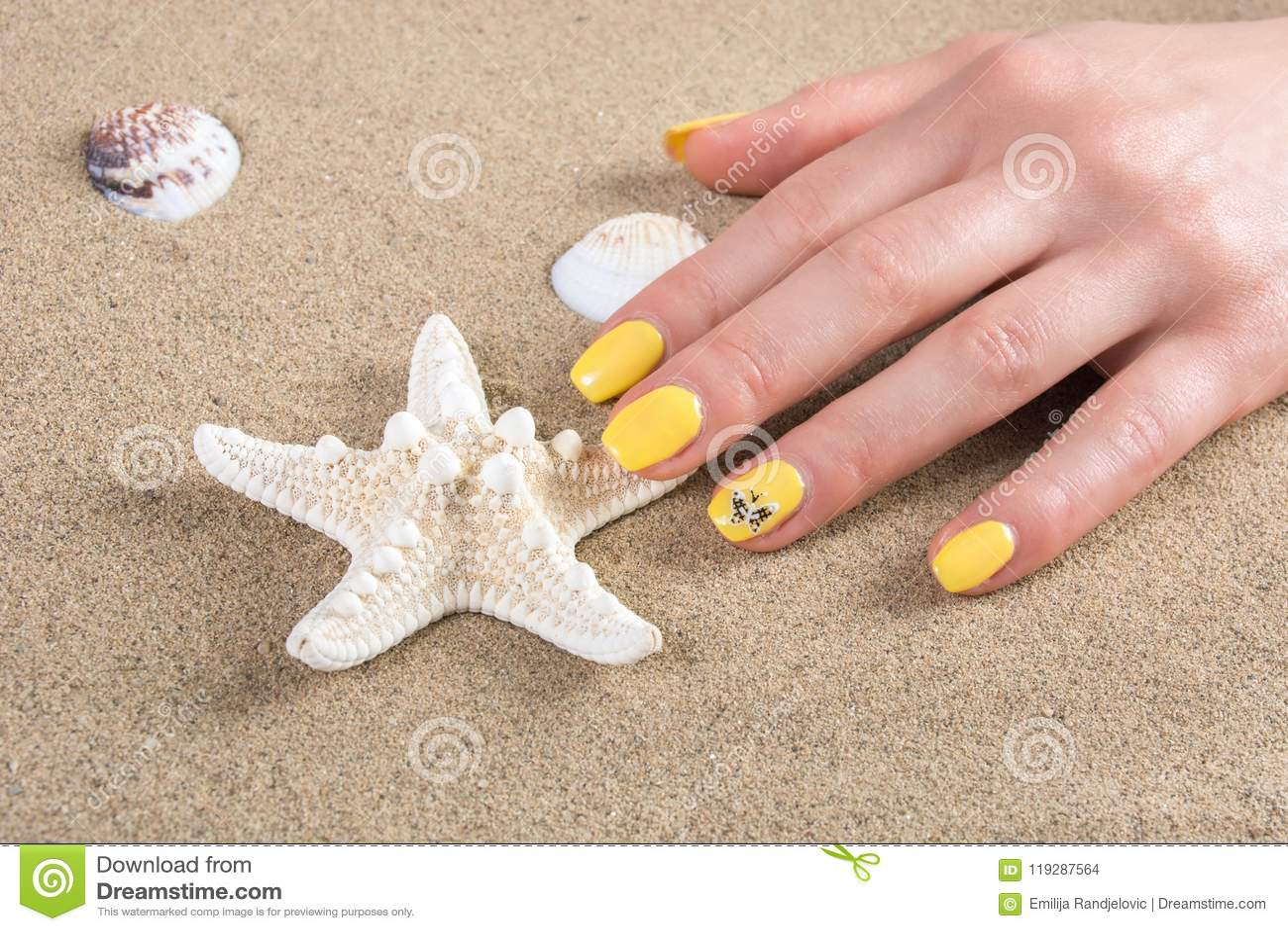 Vrouw met het gele poetsmiddel van de spijkersmanicure wat betreft zeester op overzees zand op strand