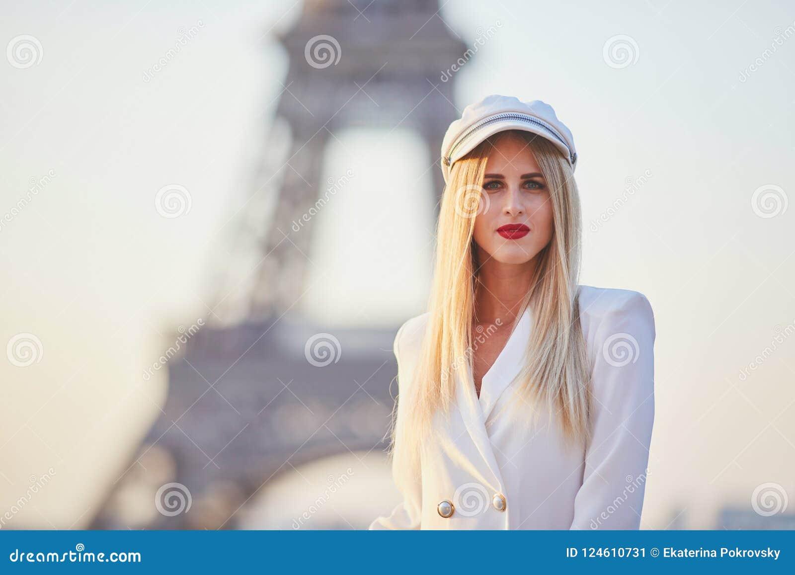 Vrouw met lang blond haar en rode lippen voor de toren van Eiffel