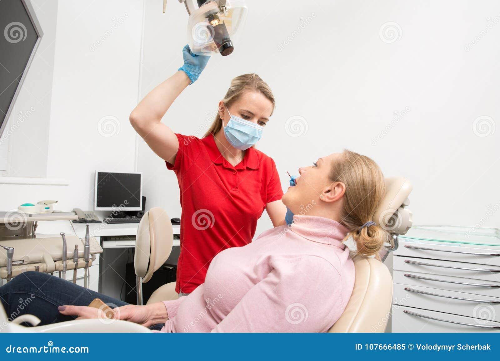 Vrouw met open mond die haar die tanden hebben door de vrouwelijke controle van tandartsTeeth op tandarts` s kantoor worden onder