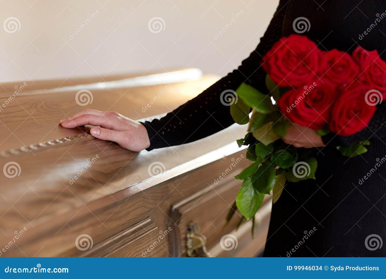 Vrouw met rode rozen en doodskist bij begrafenis