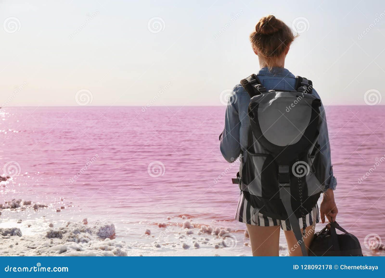 Vrouw met rugzak op kust