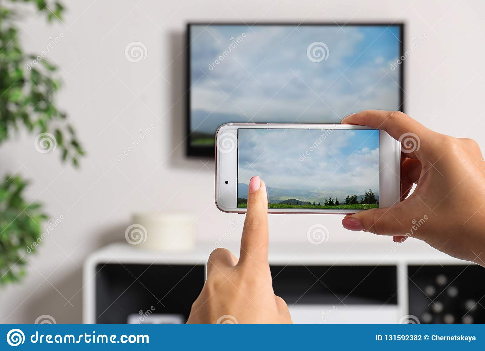 Vrouw met smartphone met Televisie wordt verbonden die