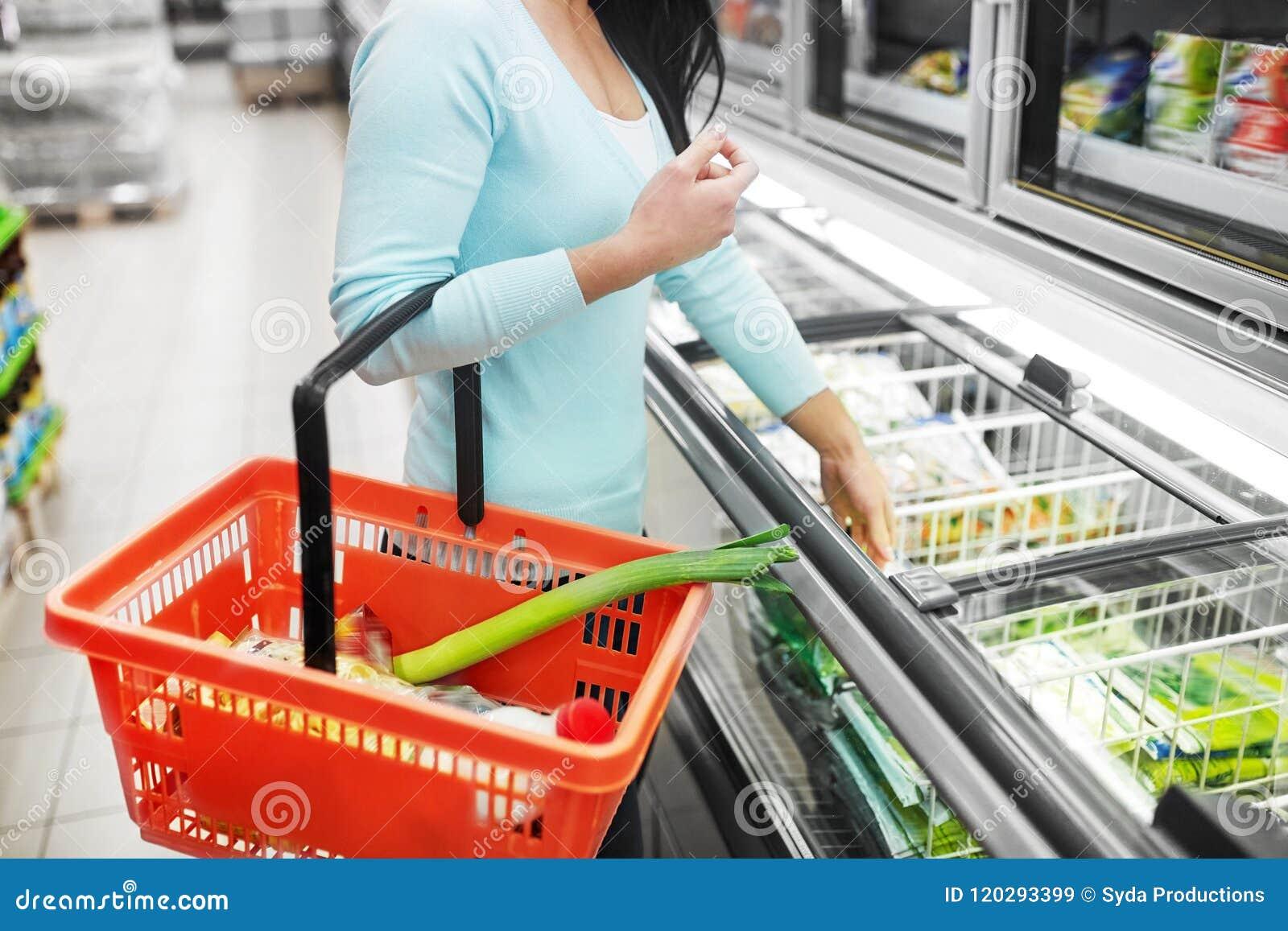 Vrouw met voedselmand bij de diepvriezer van de kruidenierswinkelopslag
