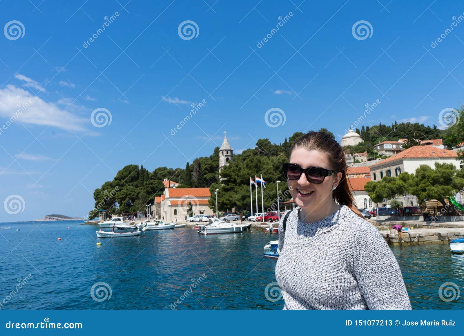 Vrouw met zonnebrilreiziger in jachtenhaven dichtbij oude stad Concept studentenreis, de zomervakantie, solo vrouwelijk toerisme,