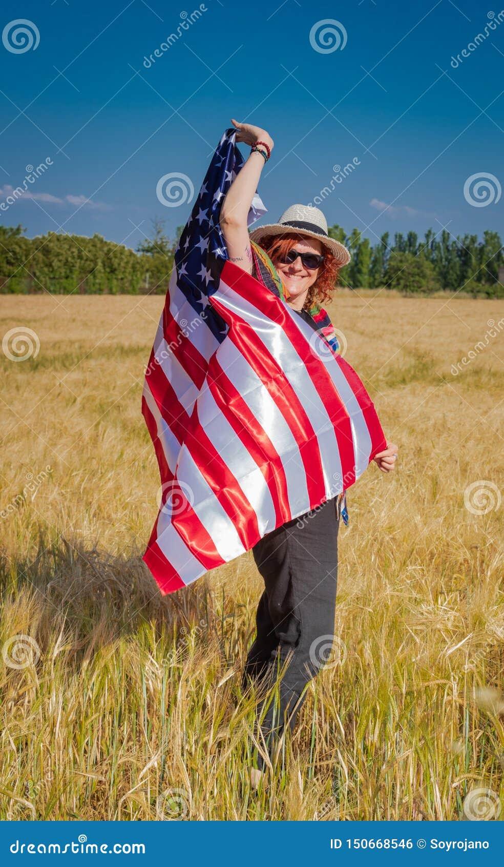 Vrouw op een tarwegebied met een vlag van de V.S.