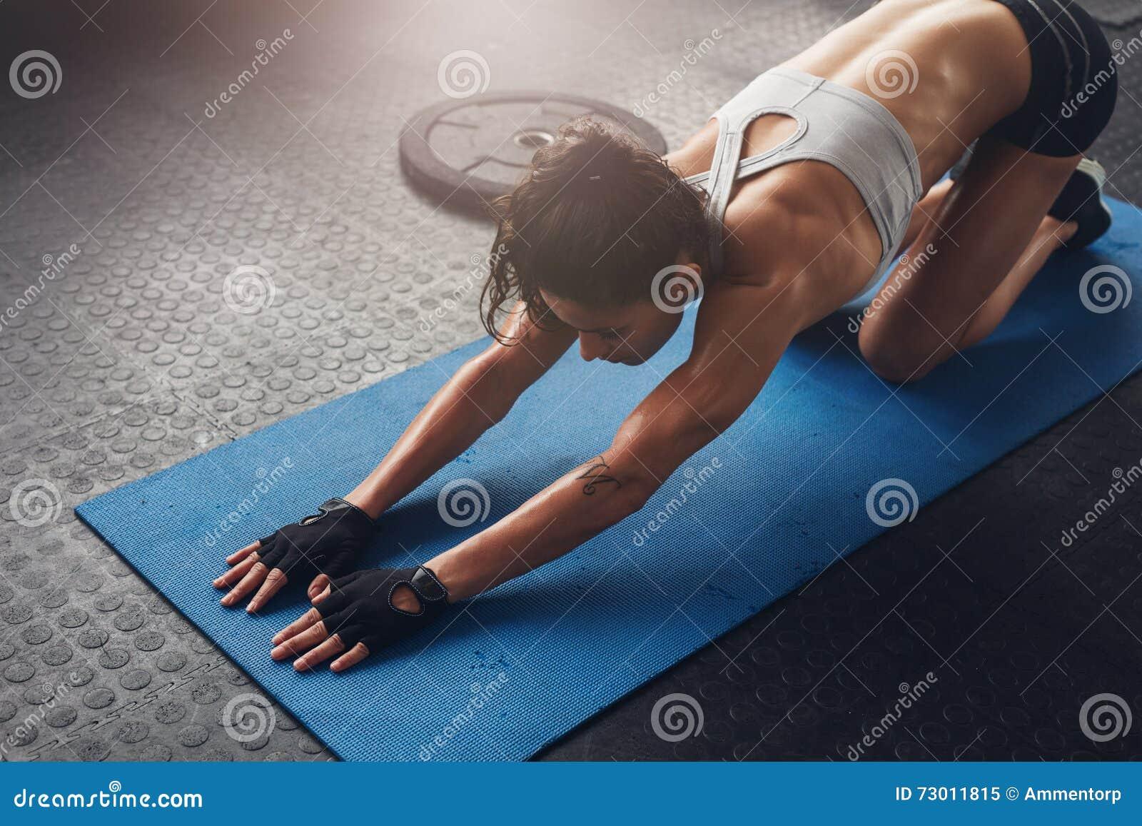 Vrouw op geschiktheidsmat die uitrekkende training doen bij gymnastiek