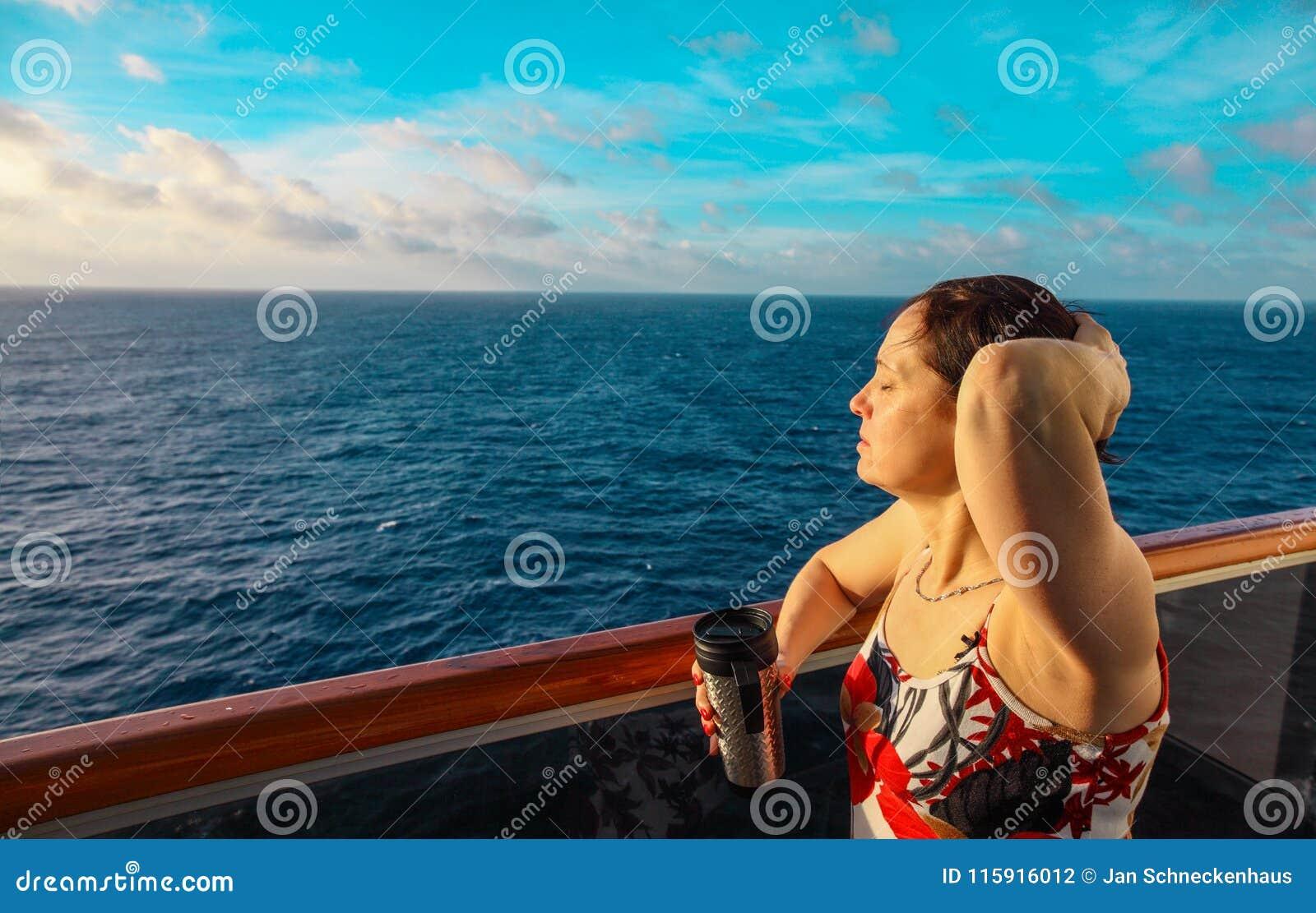 Vrouw op het balkon van een cruiseschip bij zonsopgang