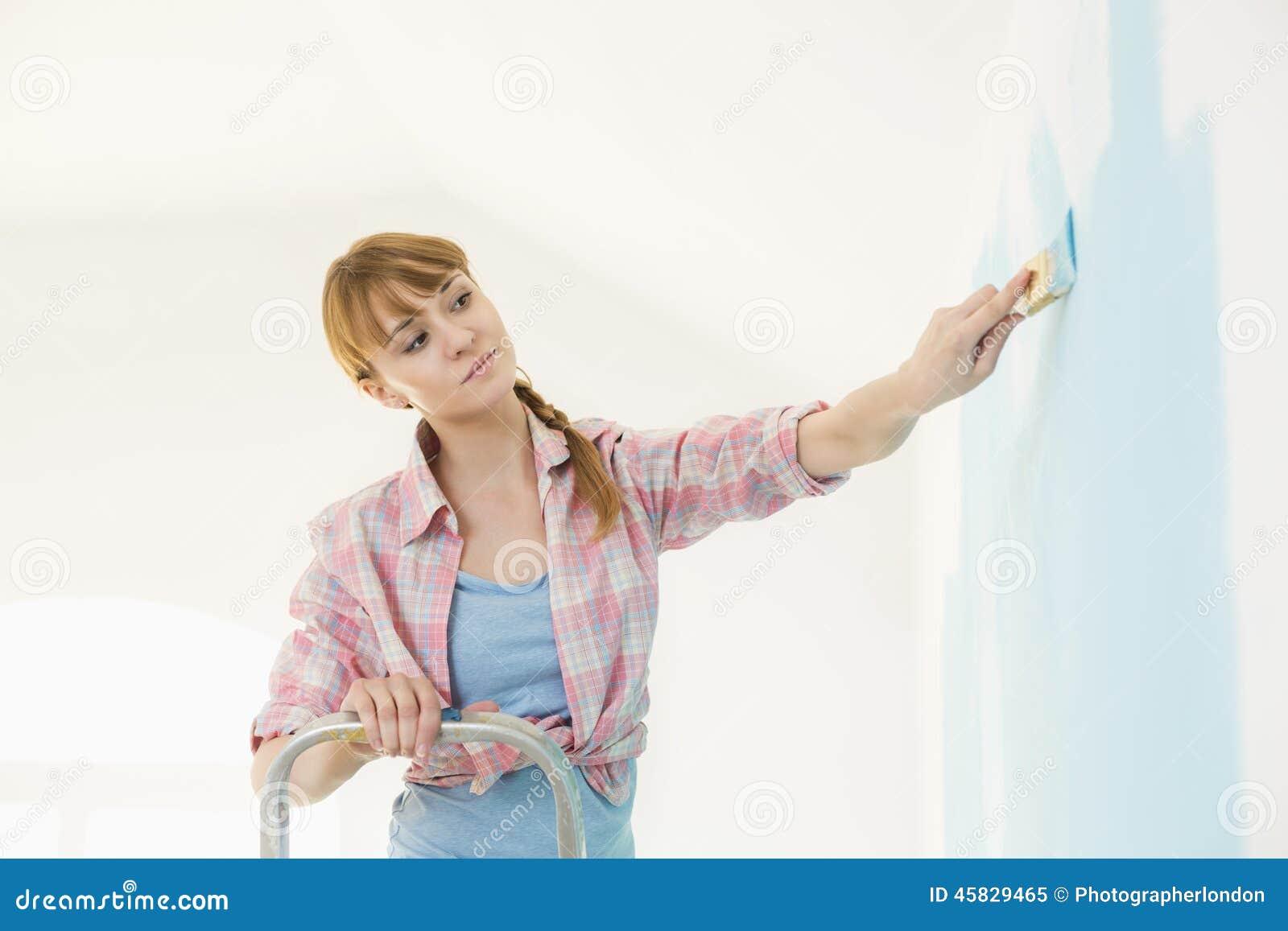 Vrouw op ladder het schilderen muur met penseel