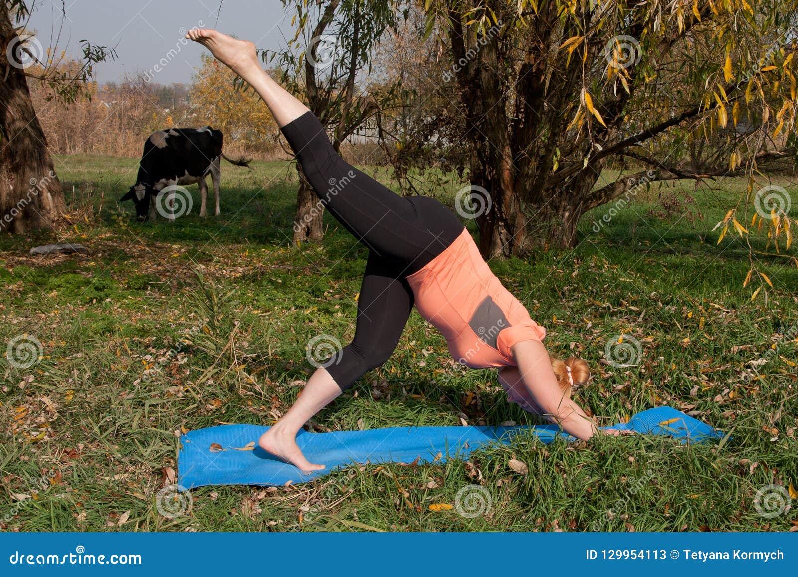 Vrouw op middelbare leeftijd in een oranje yoga van de T-shirtpraktijk in aard