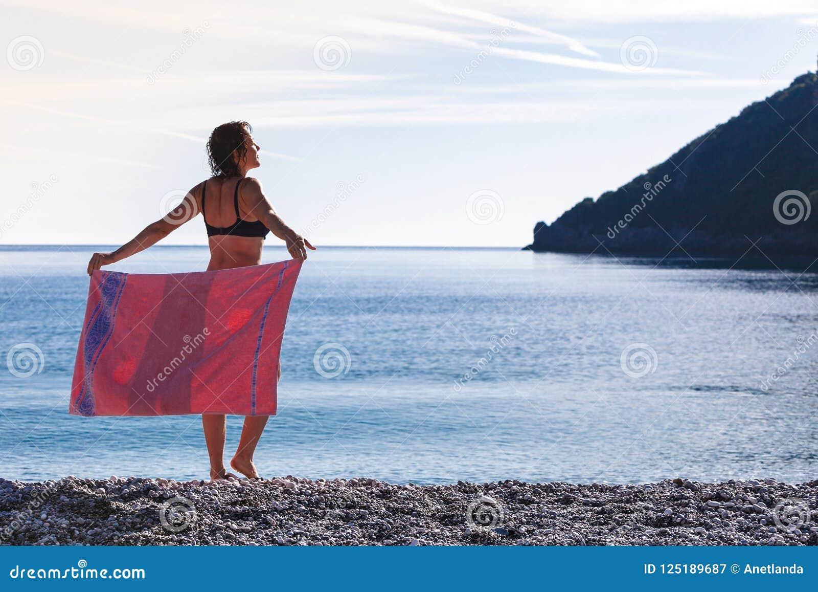 Vrouw op strand die heupen behandelen met handdoek