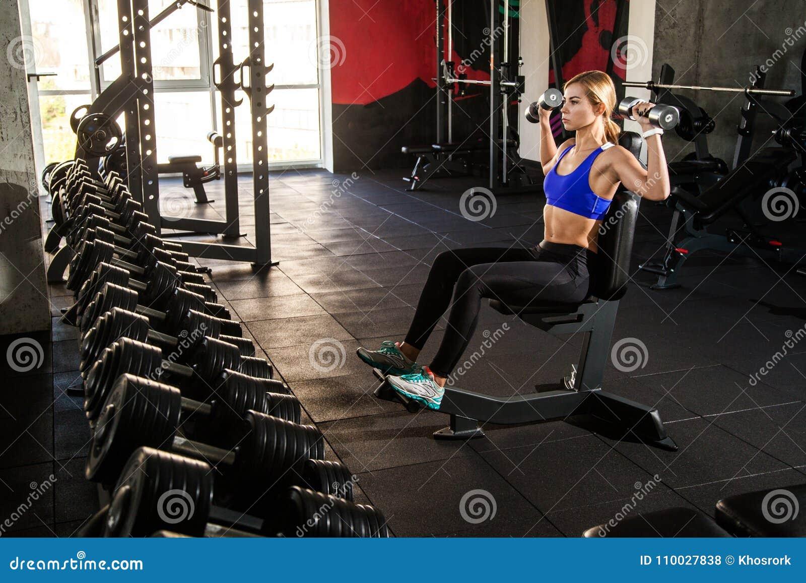 Vrouw opleidingsbicepsen en triceps met domoren op gymnastiek