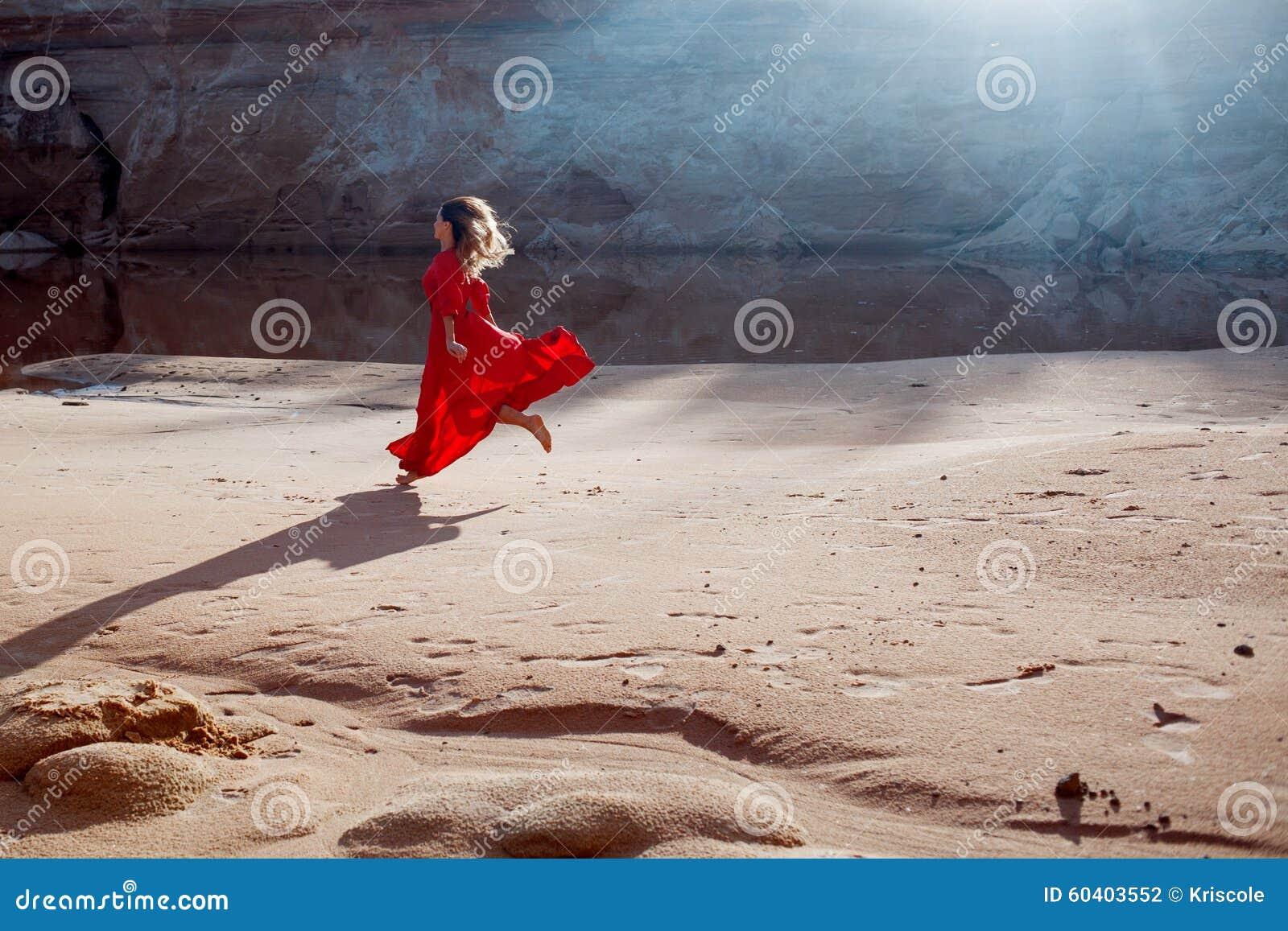 Vrouw in rode golvende kleding met het vliegen stoffenlooppas