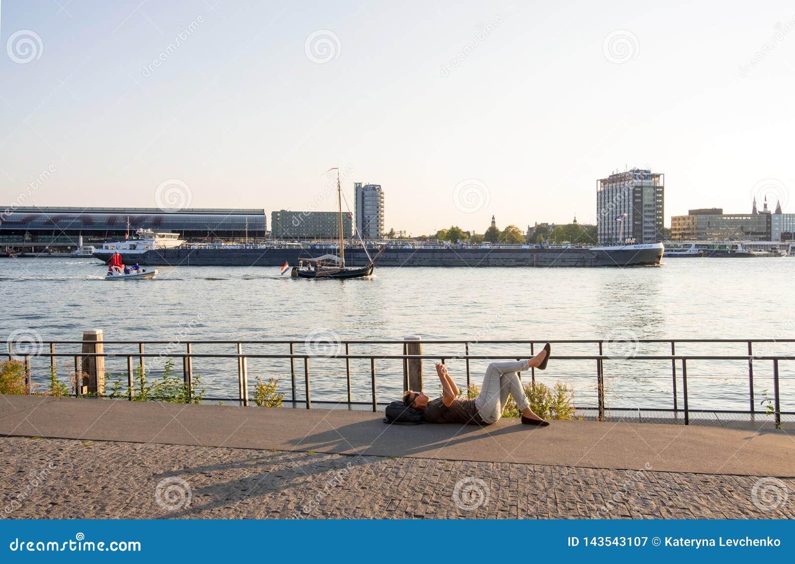 Vrouw rusten die op de Amstel-Rivierkust tegen de achtergrond van de haven en de Centrale Post in Amsterdam liggen