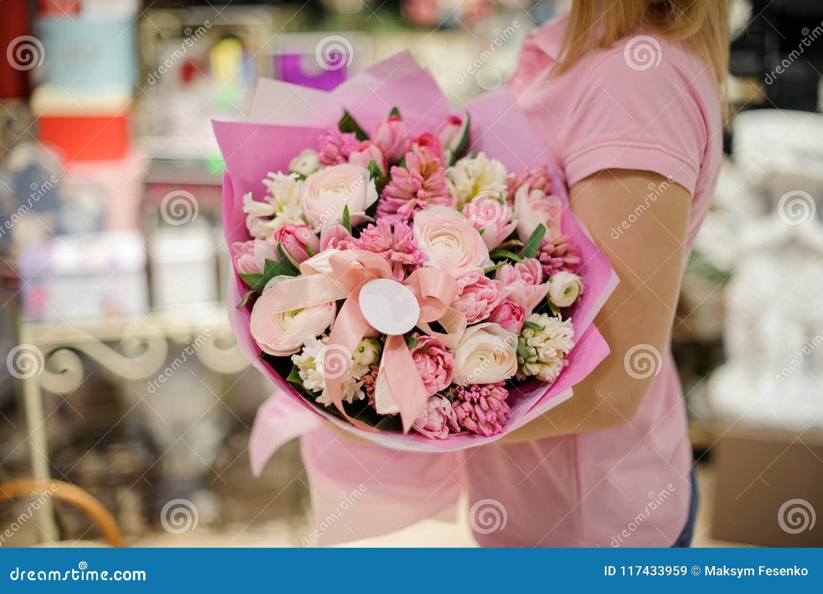 Vrouw tedere roze bloemsamenstelling houden die bestaand uit rozen, ranunculus en andere mooie bloemen