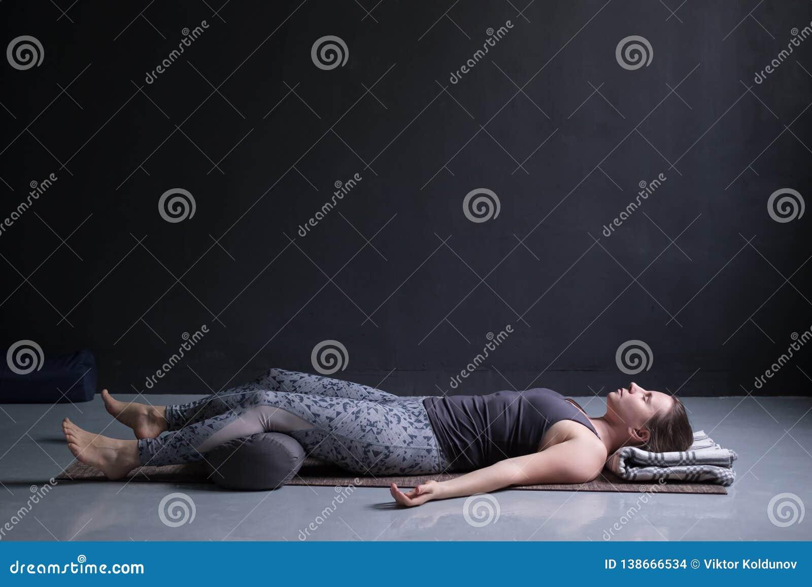 Vrouw uitwerken, die yogaoefening op houten vloer doen, die in Shavasana liggen