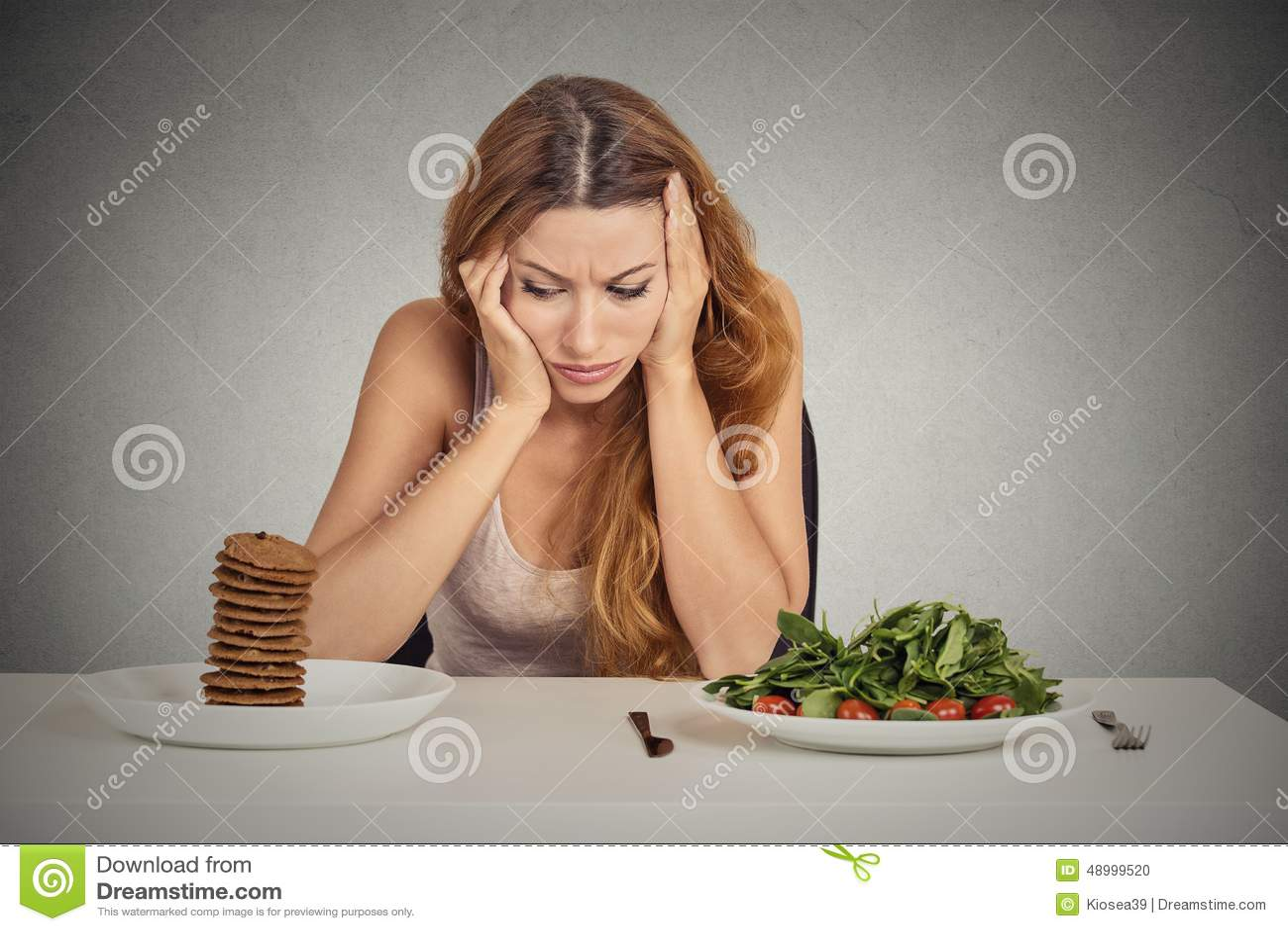 Vrouw van dieetbeperkingen wordt vermoeid die gezond voedsel of zoete koekjes beslissen te eten dat