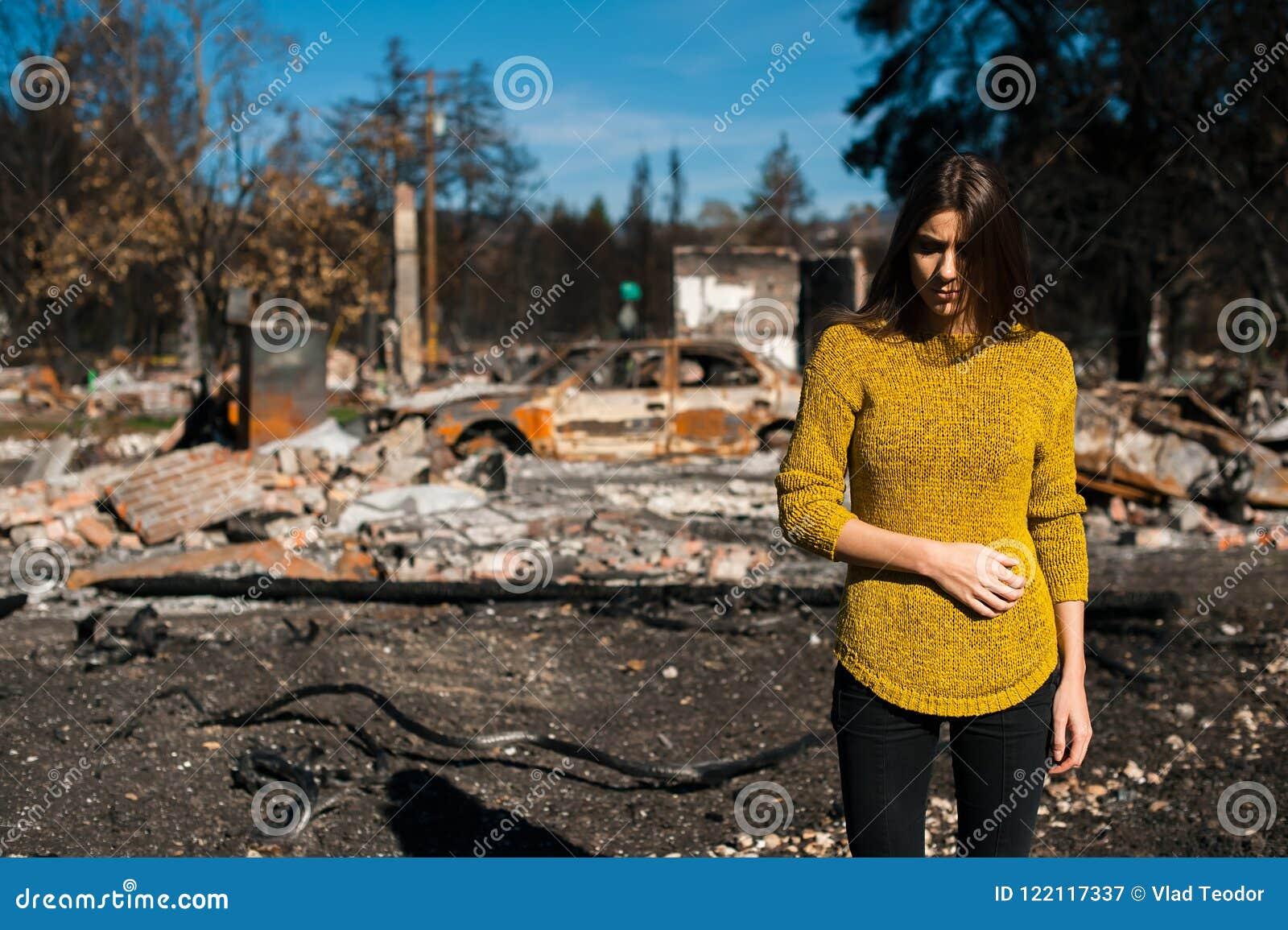 Vrouw voor haar gebrand huis na brandramp