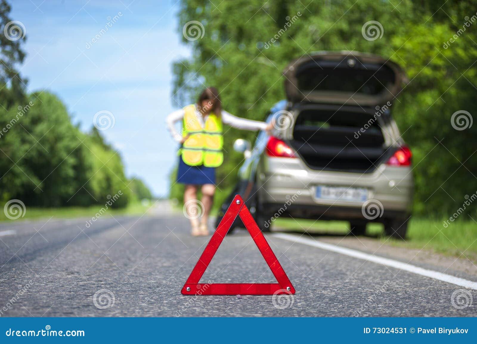 Vrouw in weerspiegelende vest dichtbij gebroken auto