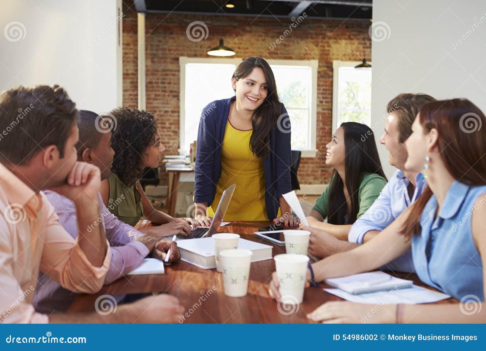 Vrouwelijk Chef- Addressing Office Workers op Vergadering