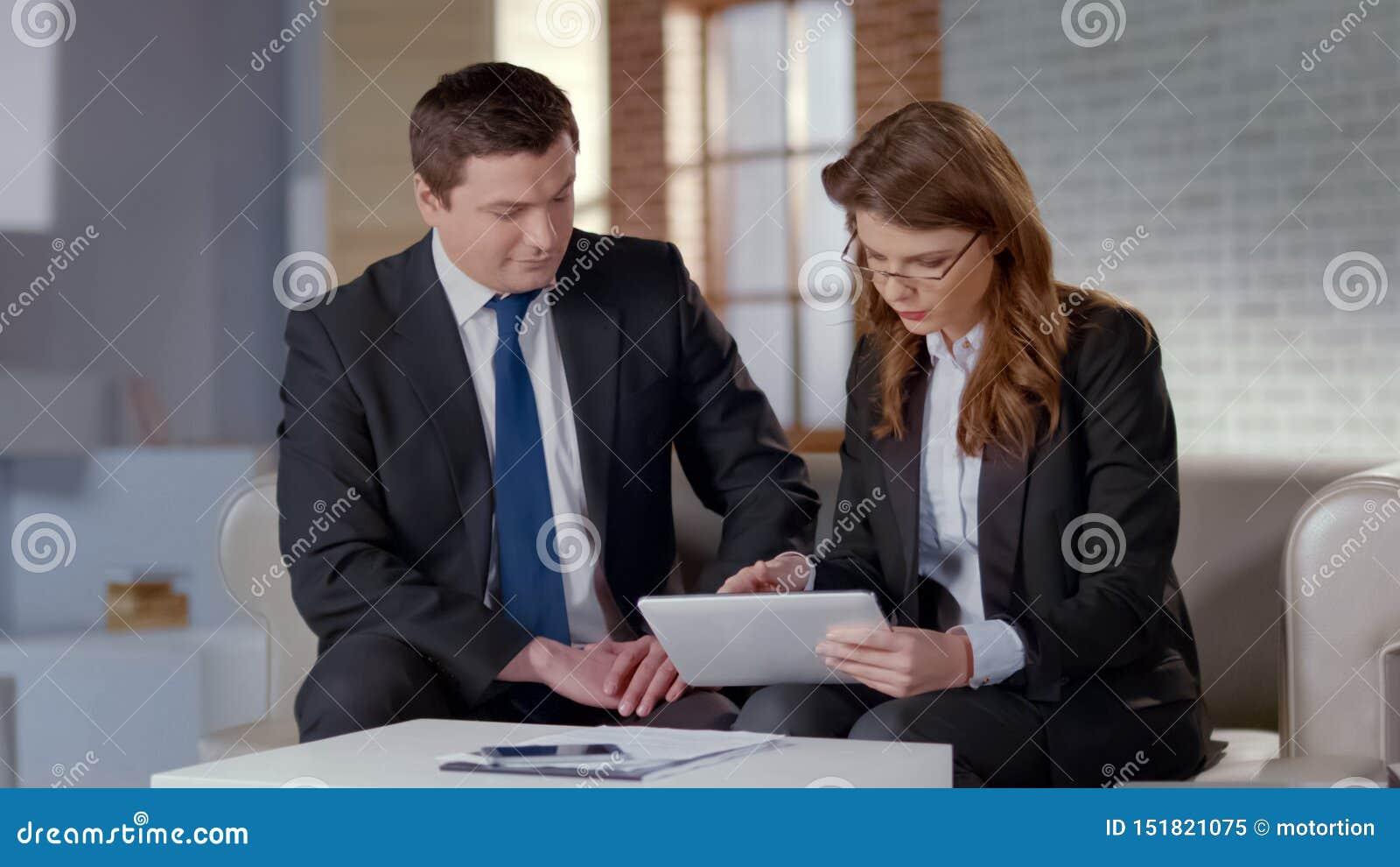 Vrouwelijk hulp het bespreken businessplan met CEO, die project op tablet tonen