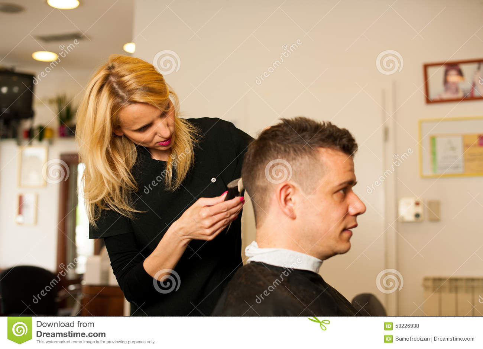 Vrouwelijk kapper scherp haar van glimlachende mensencliënt bij schoonheid