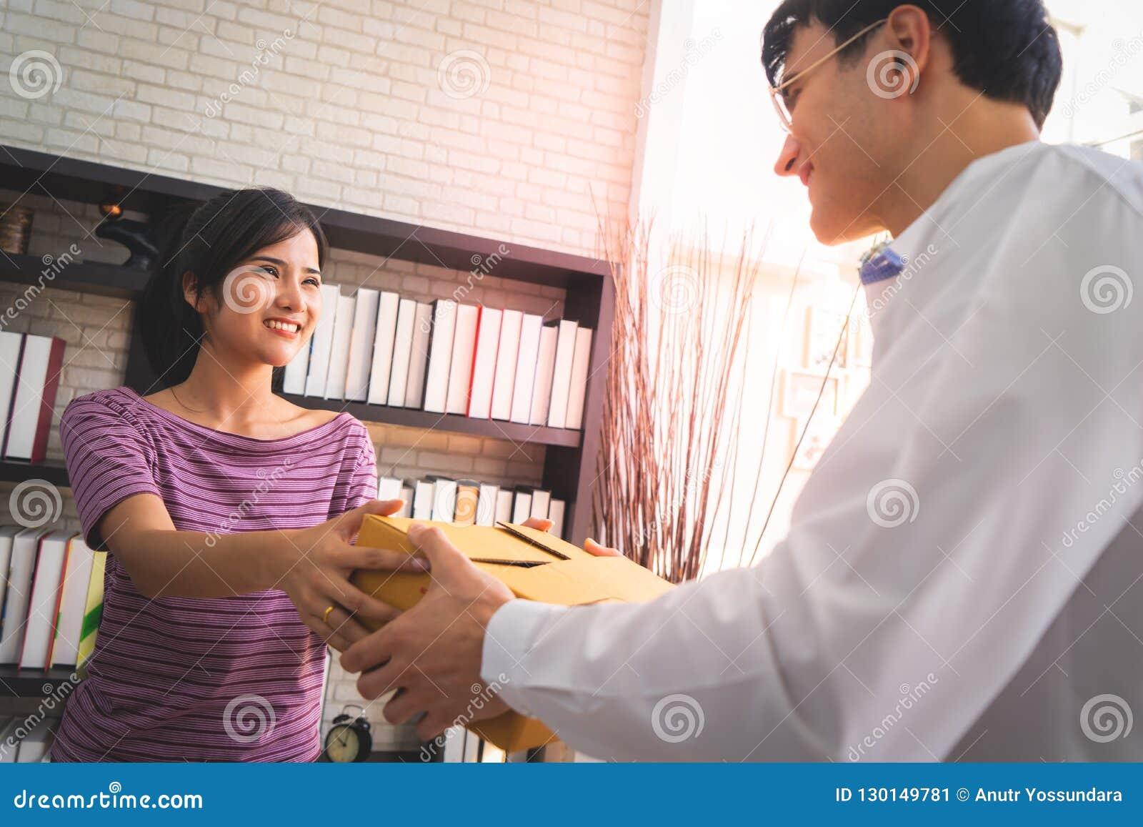 Vrouwelijk van het bedrijfs verkopershuis eigenaar behandelend pakket aan klant