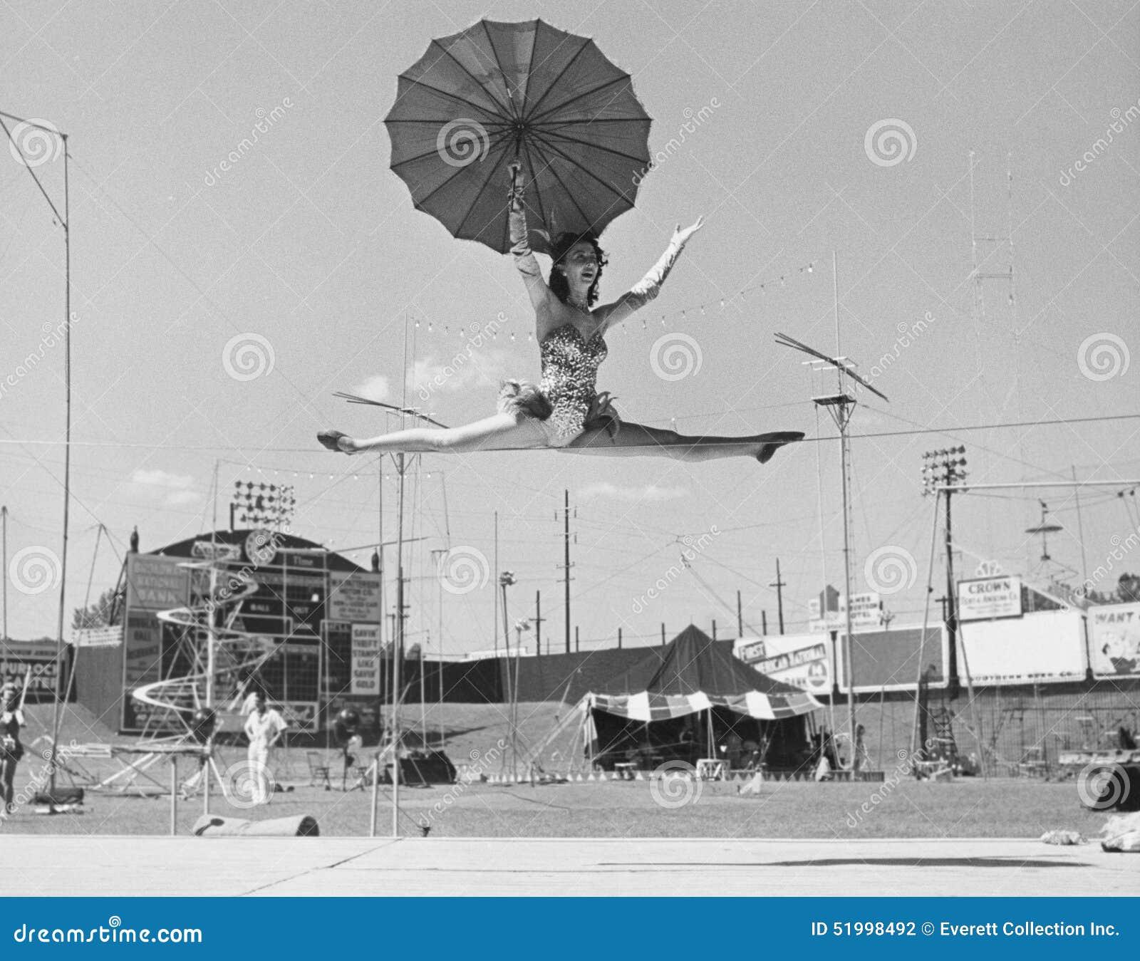 Vrouwelijke acrobaat die spleten op strak koord doen (Alle afgeschilderde personen leven niet langer en geen landgoed bestaat Th
