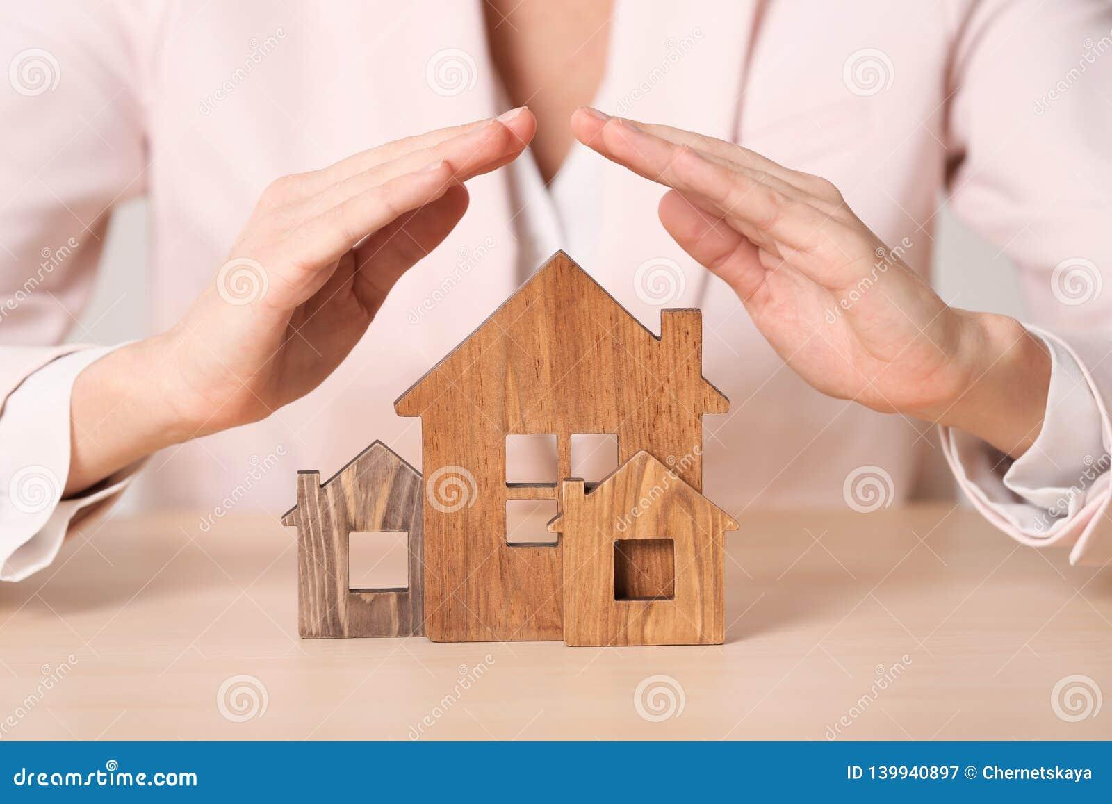Vrouwelijke agent die blokhuizen behandelen bij lijst De verzekering van het huis