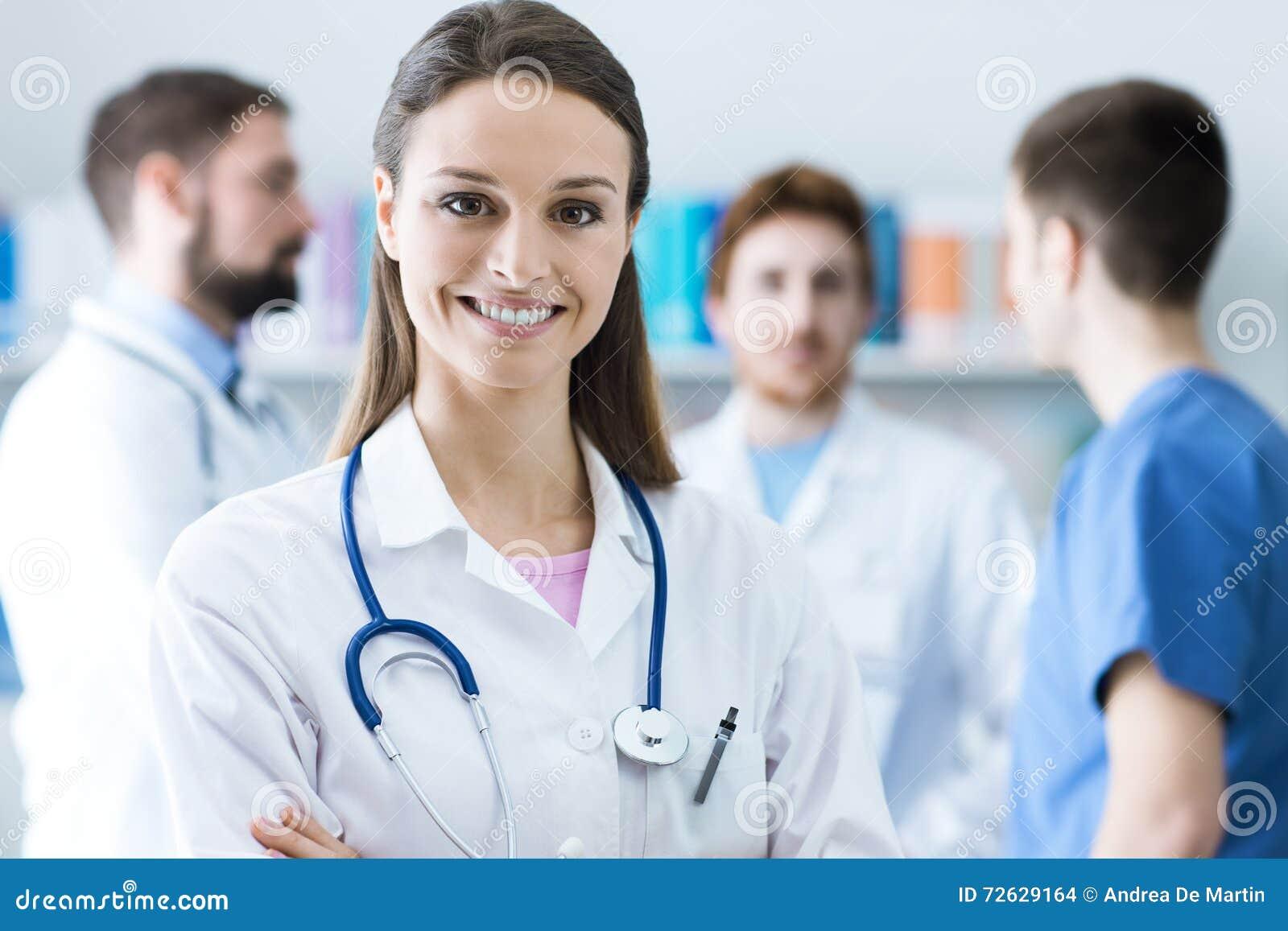 Vrouwelijke arts die bij camera glimlachen