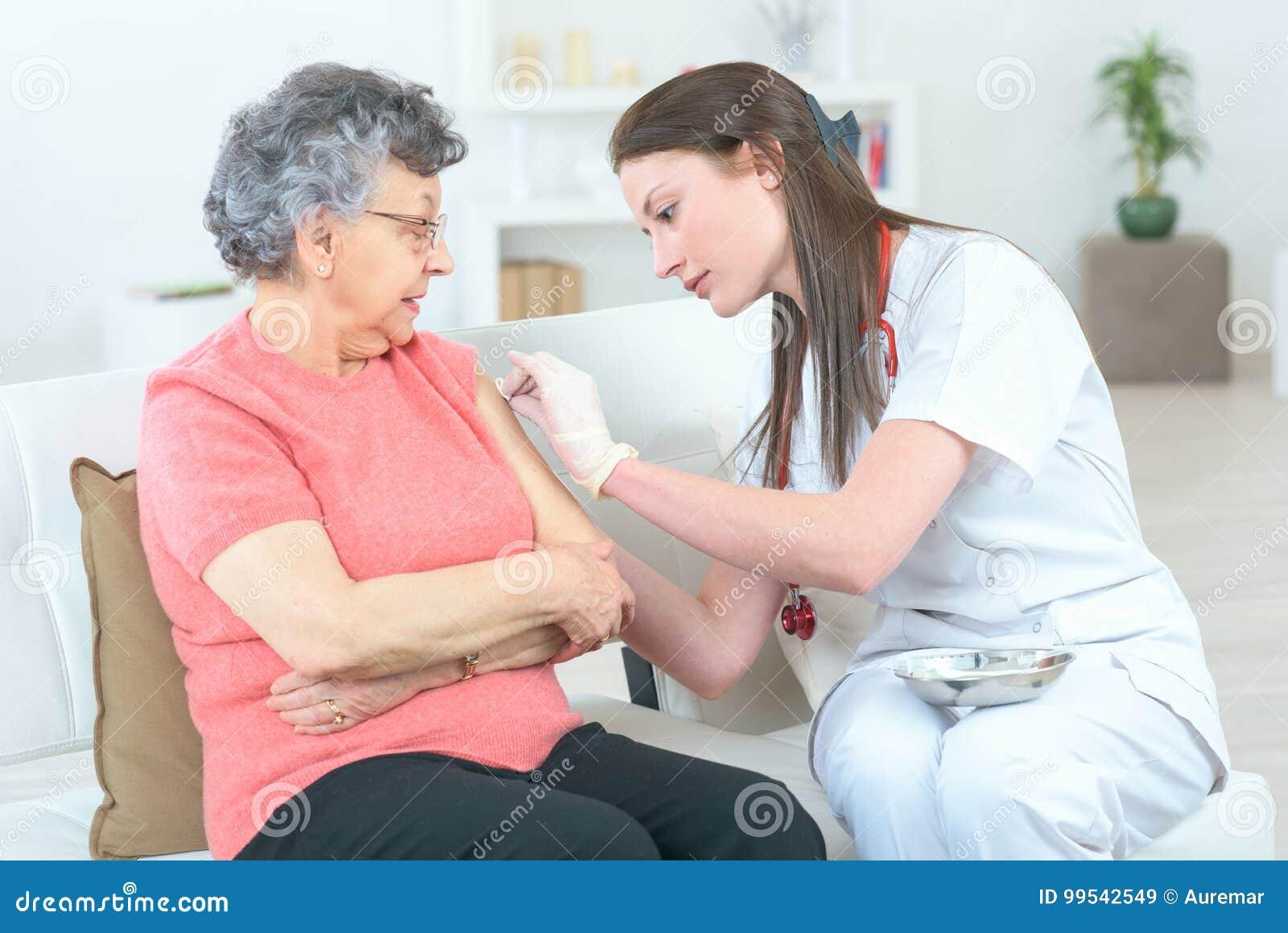Vrouwelijke arts die injectie geven aan bejaarde patiënt