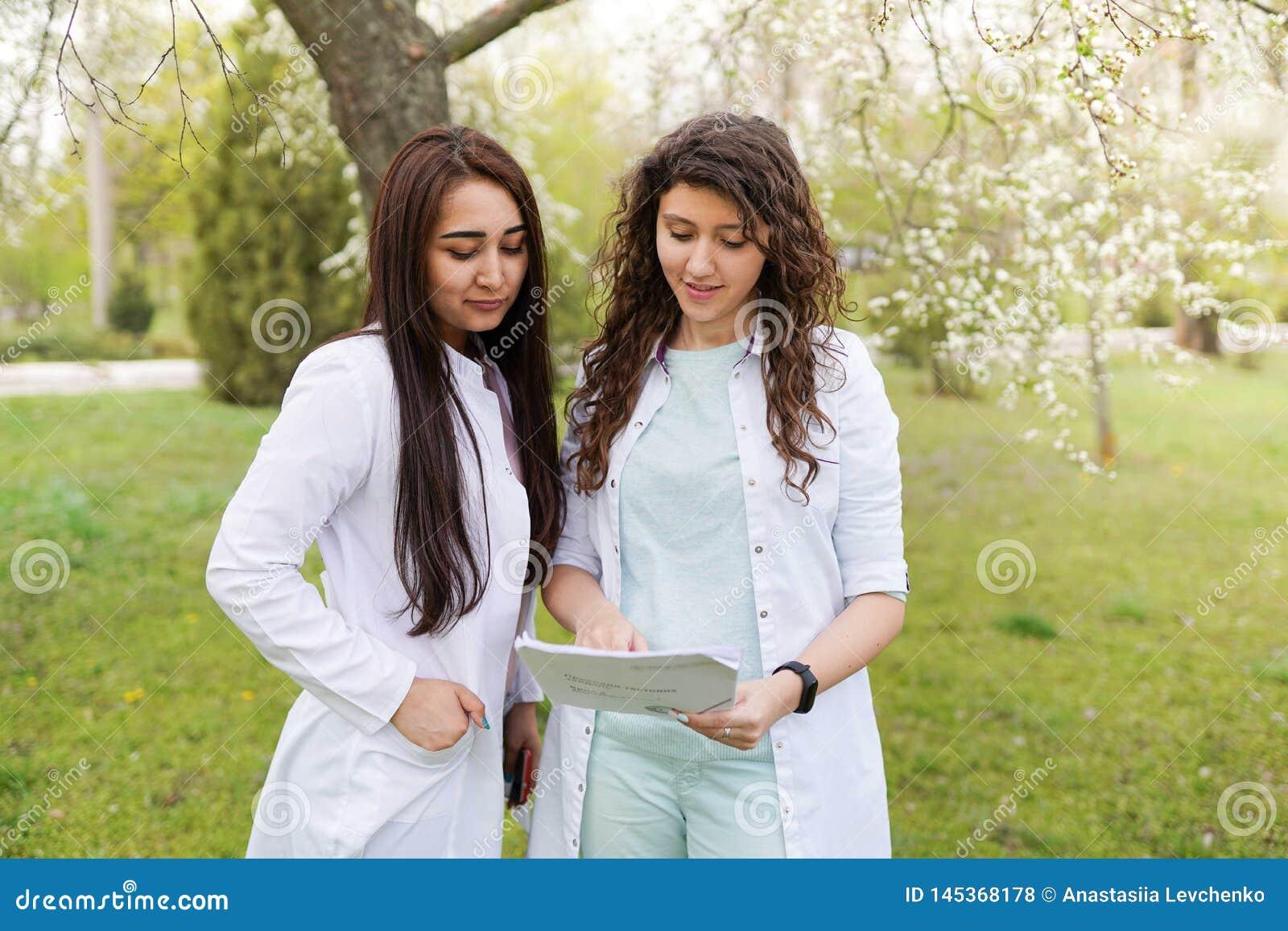 Vrouwelijke artsen in openlucht Medische achtergrond de studenten dichtbij het ziekenhuis in bloem tuinieren