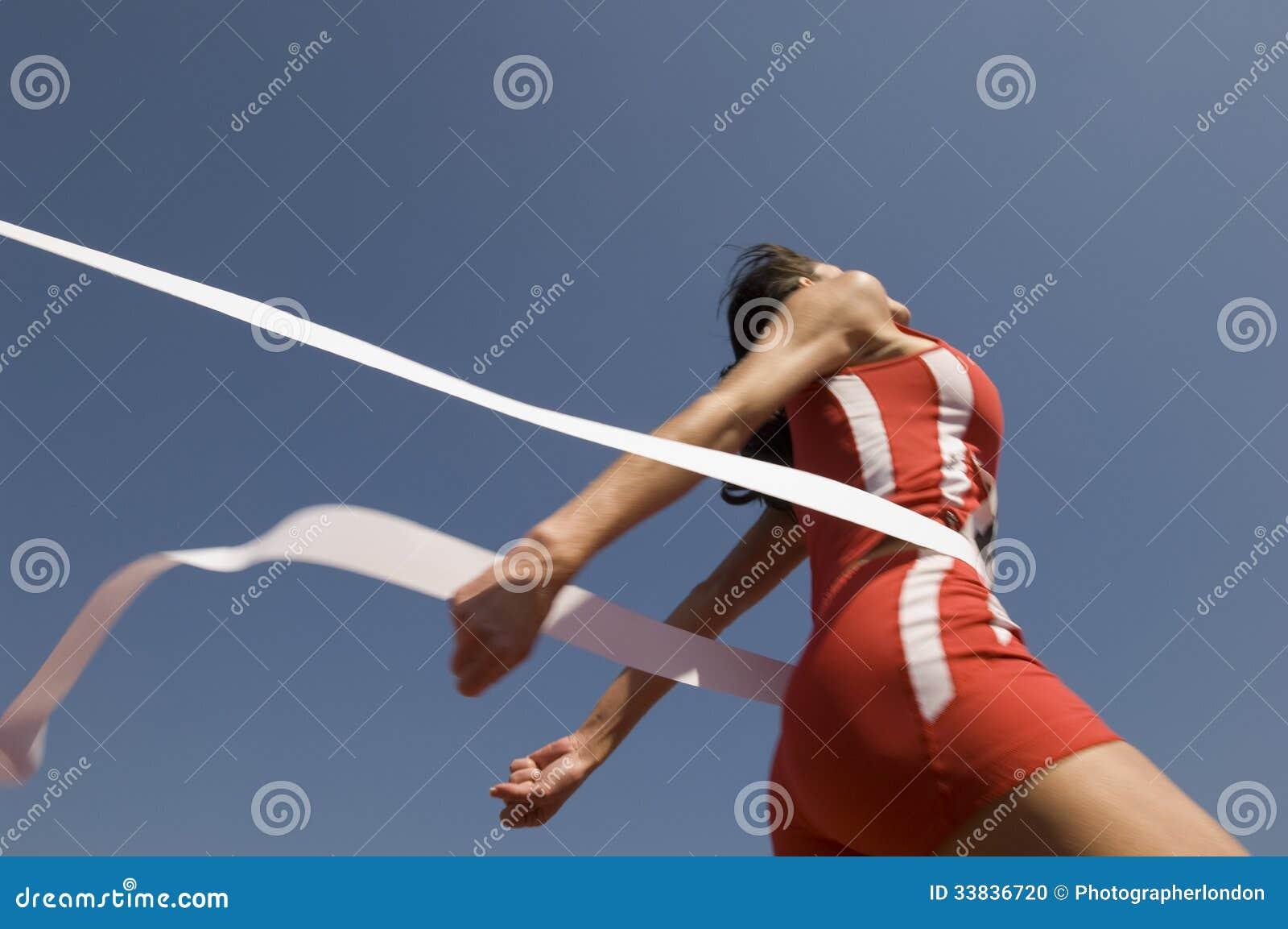 Vrouwelijke Atleet Crossing Finish Line tegen Blauwe Hemel