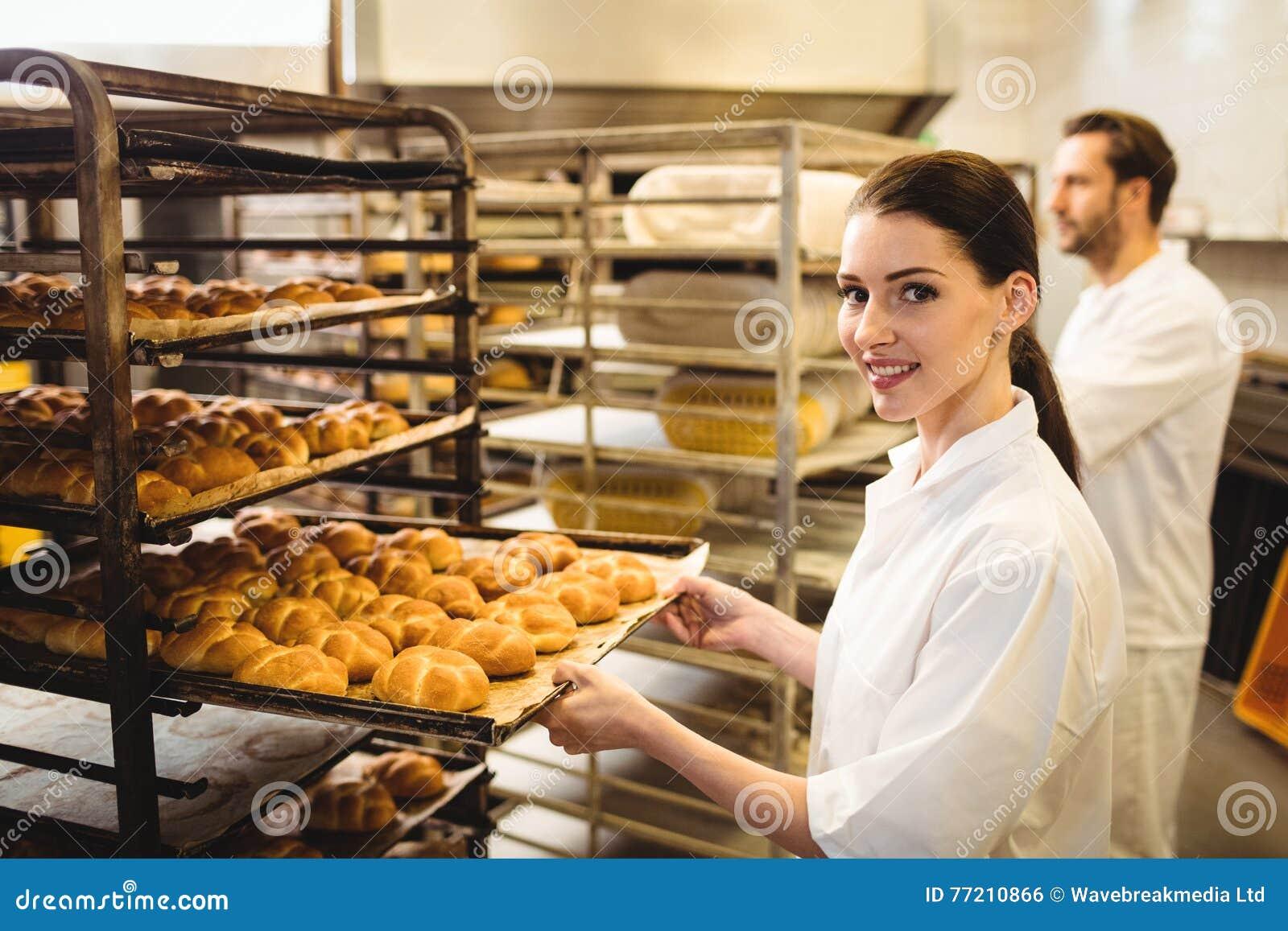 Vrouwelijke bakker die een dienblad van michetta houden