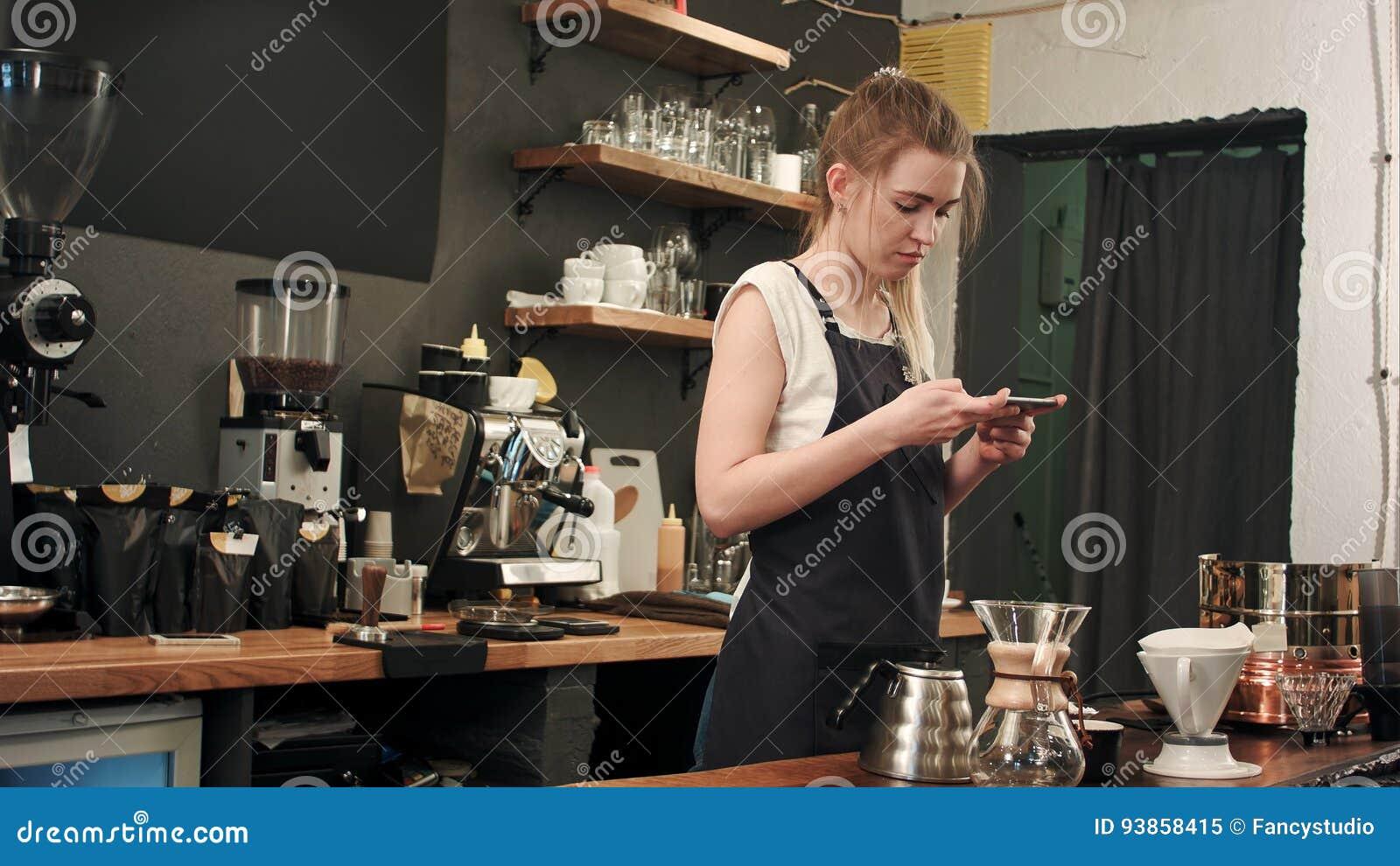 Vrouwelijke barista die beelden van voorbereide cofee met smartphone nemen