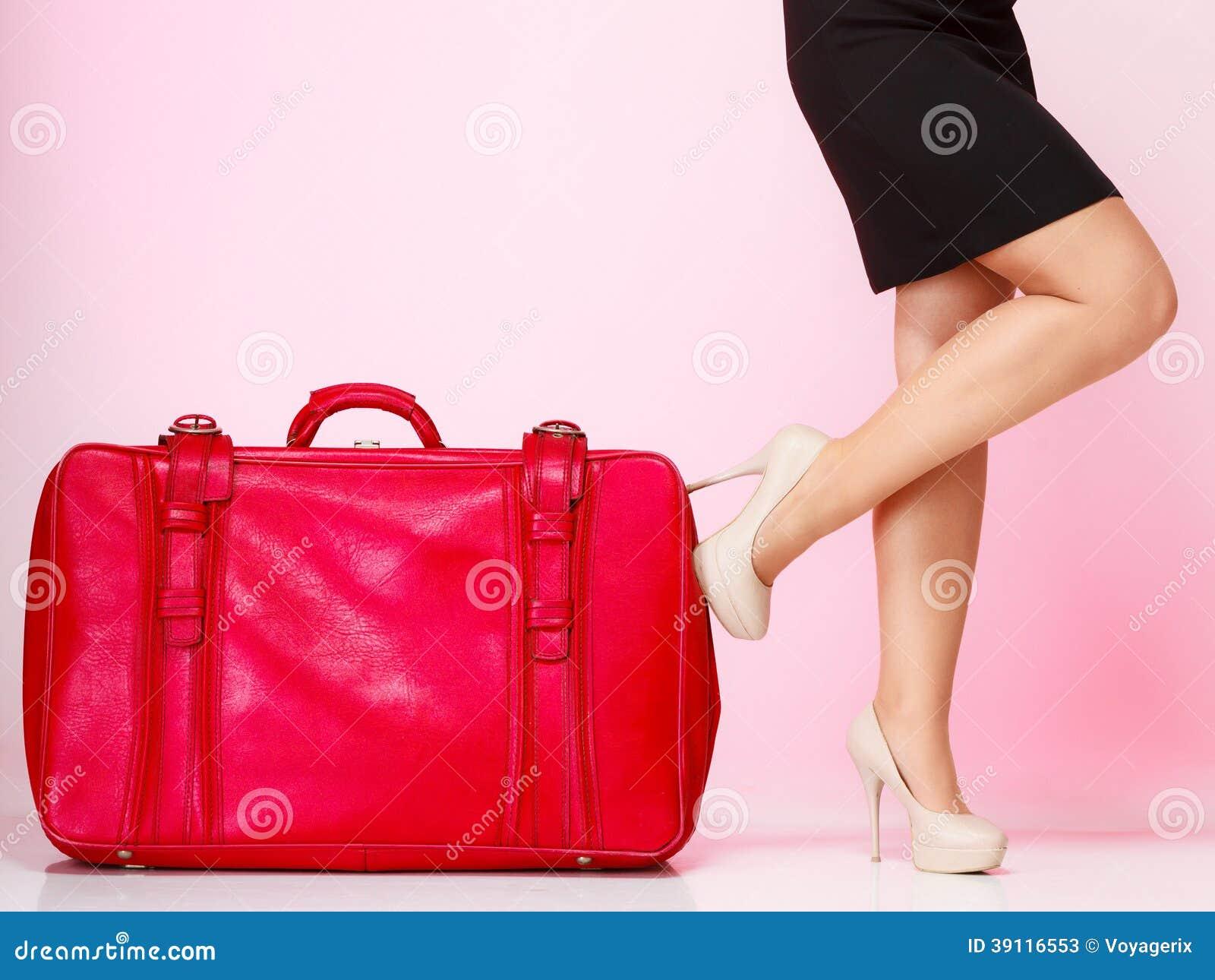Vrouwelijke benen met rode koffer op roze. Reis.
