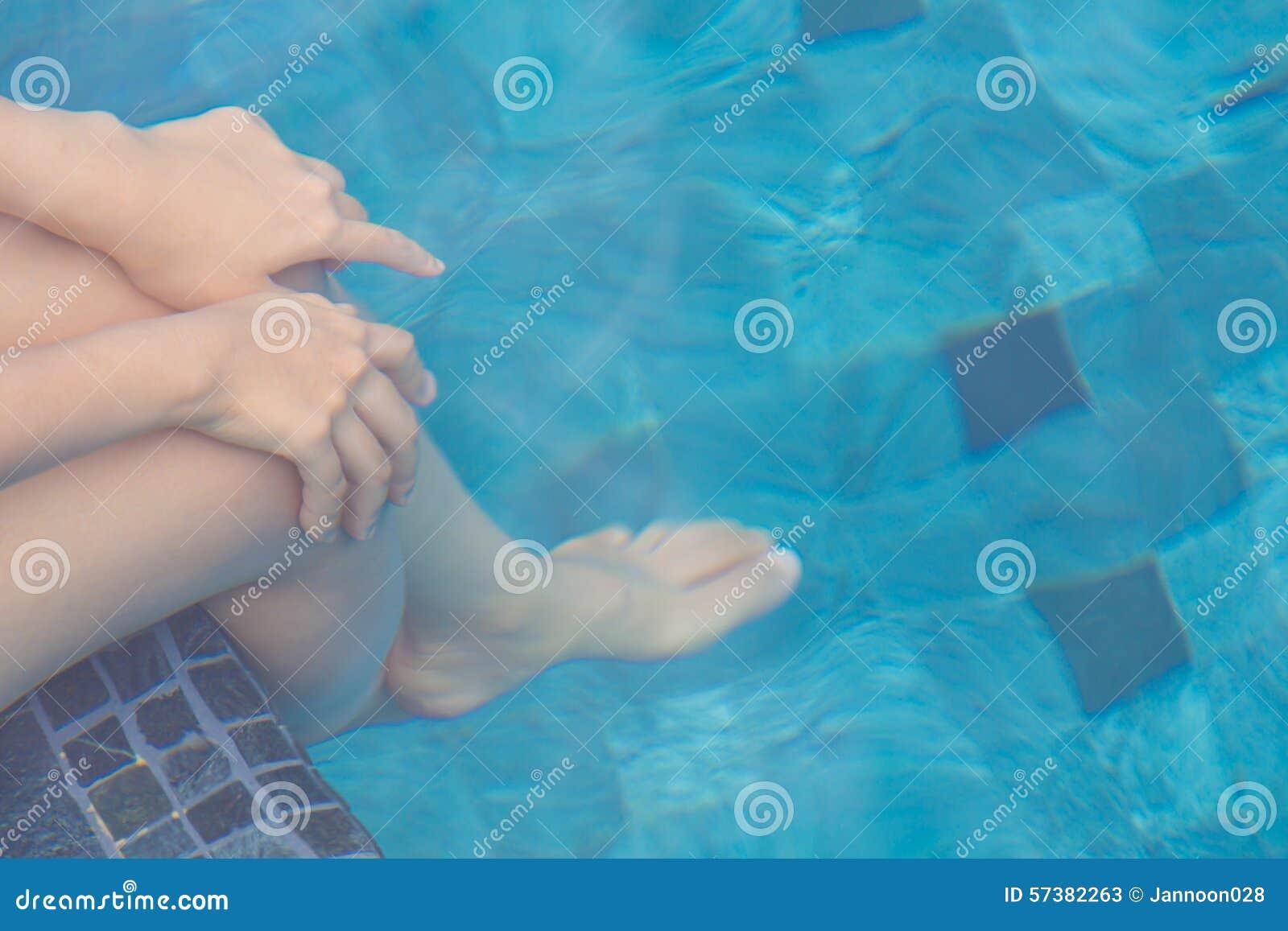 Vrouwelijke benen onder het zwembad