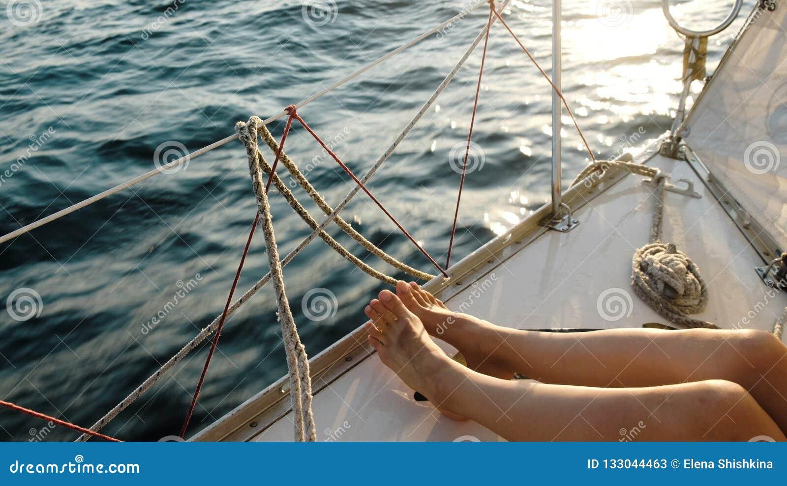 Vrouwelijke benenvoeten op de varende jachtclose-up in de open zee
