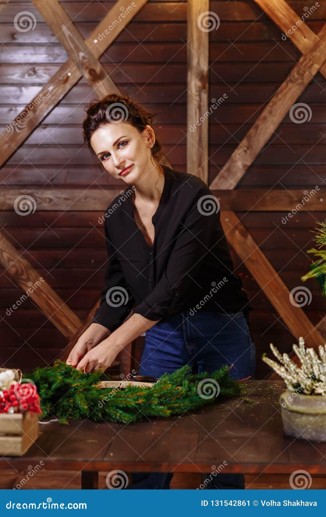 Vrouwelijke bloemist die Kerstmiskroon in bloemwinkel verfraaien Vrouw die Juwelen voor Kerstmisvakantie maken Het maken van Deco