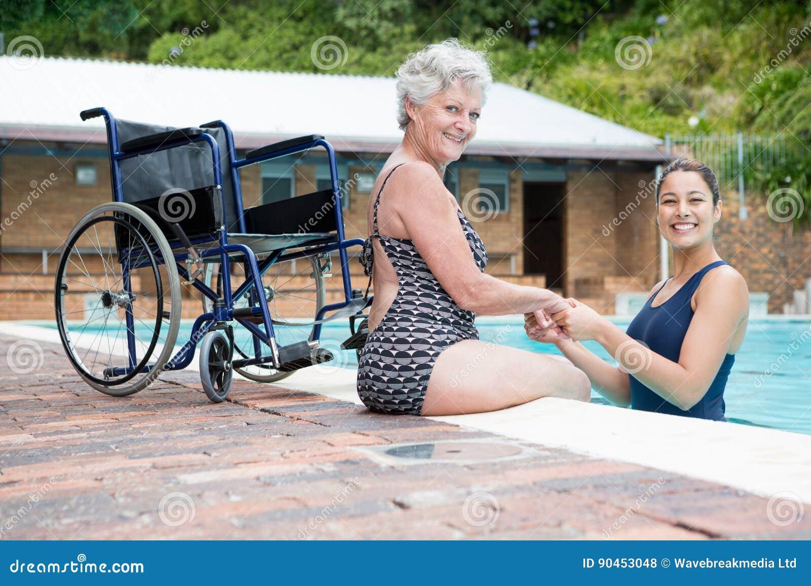 Vrouwelijke bus en hogere vrouw die bij poolside glimlachen