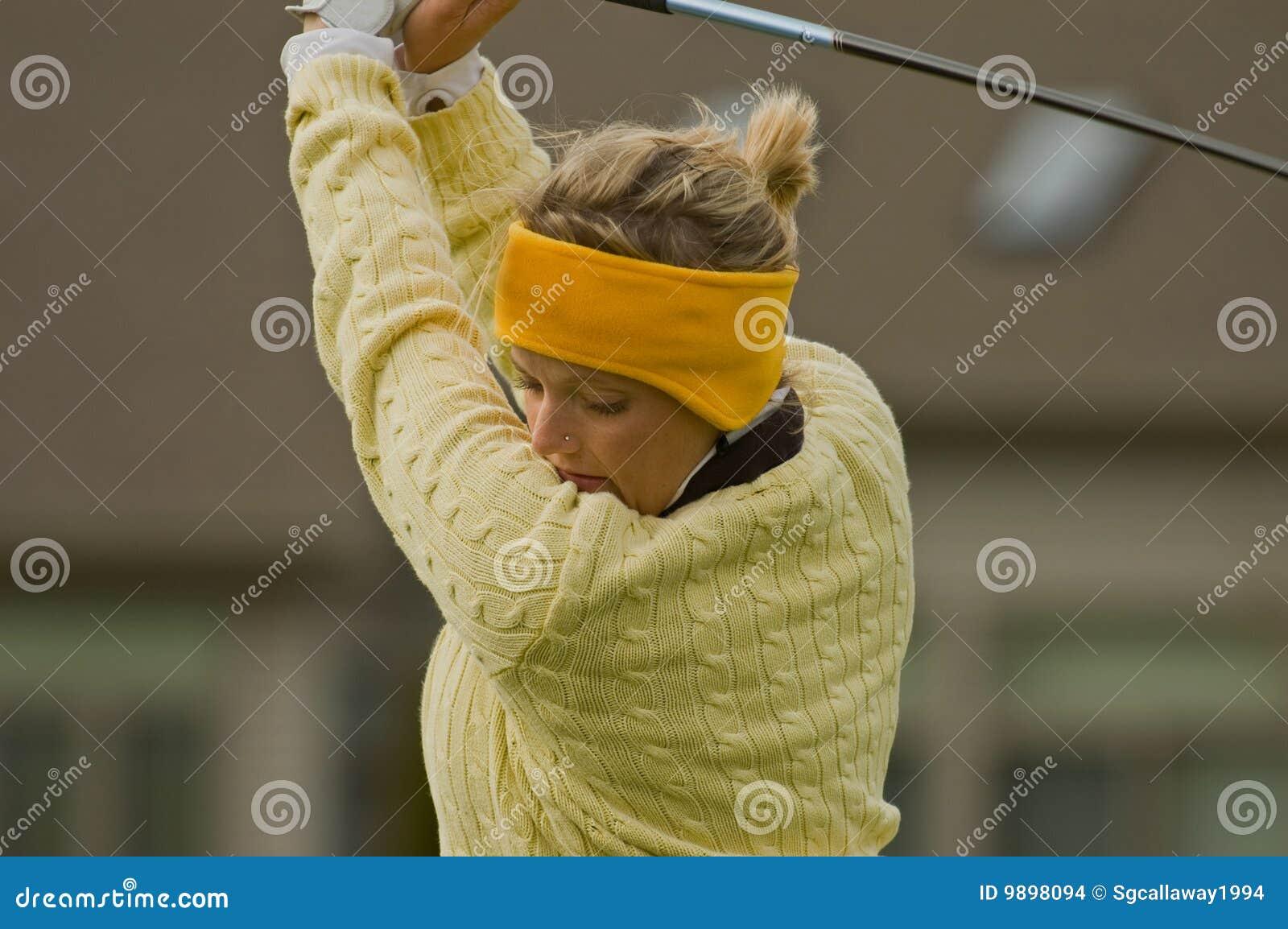 Vrouwelijke collegiale golfspeler slingerende golfclub