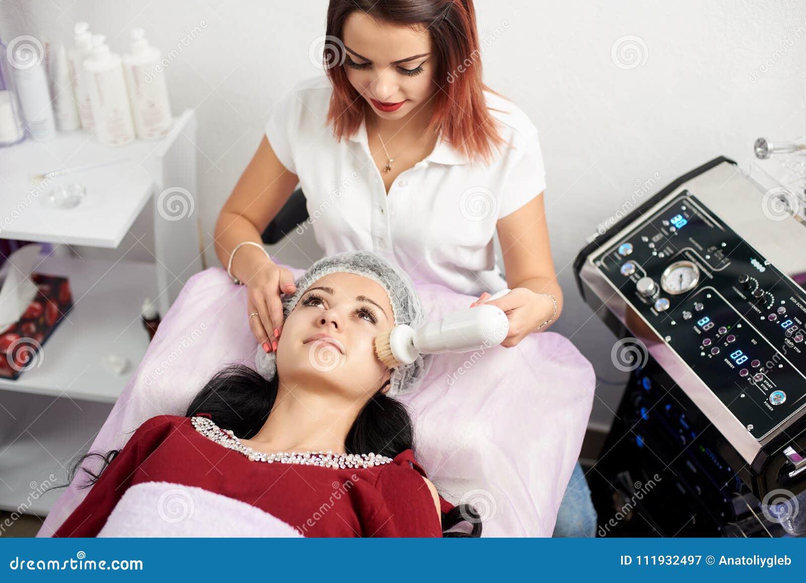 Vrouwelijke cosmetologist geeft het gezichts schoonmaken met een roterende borstel aan een mooie donkerbruine vrouw in een schoon