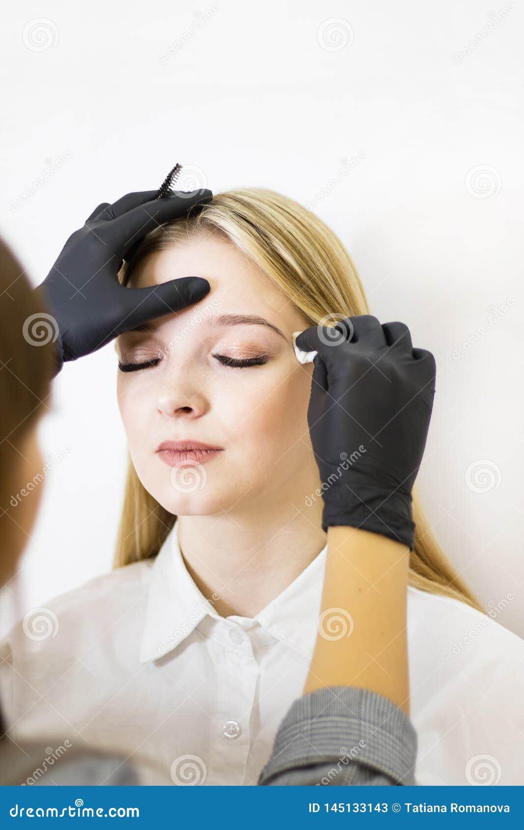 Vrouwelijke cosmetologist voert wenkbrauwcorrectie op mooie modellen in de schoonheidssalon uit Het gezicht van het meisje is een