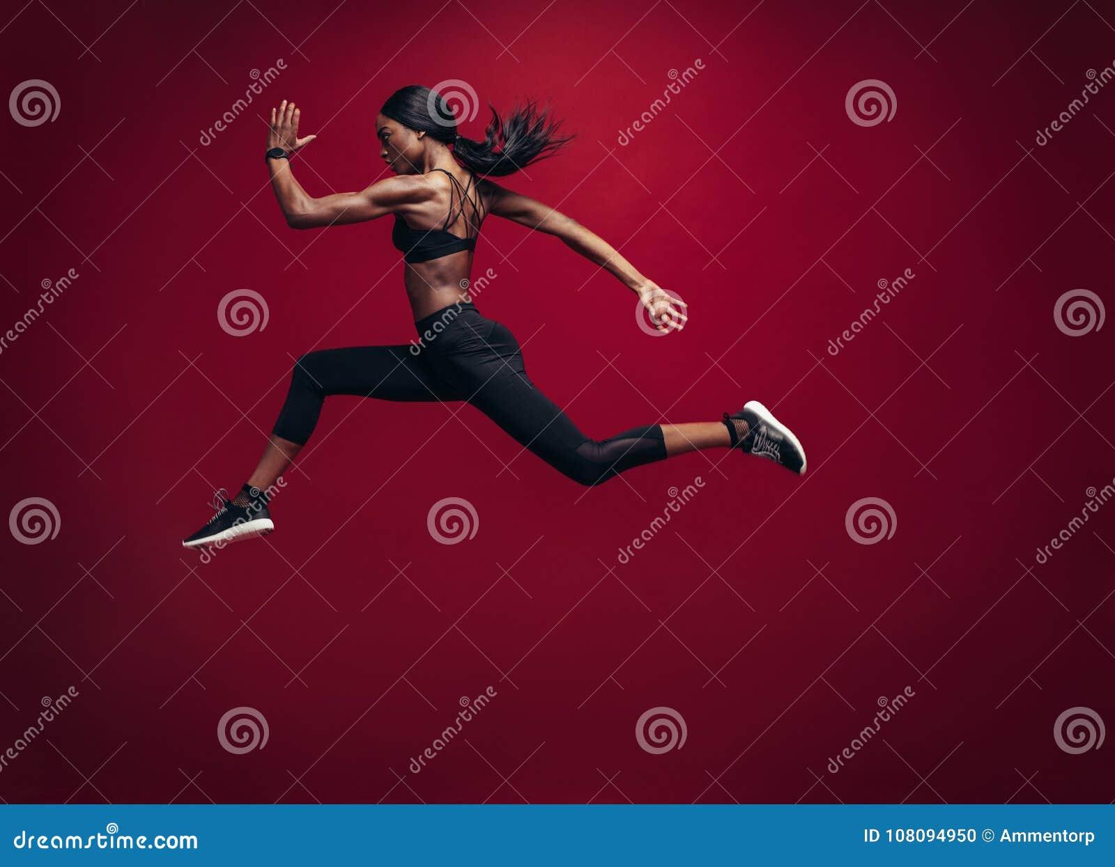 Vrouwelijke en atleet die lopen springen