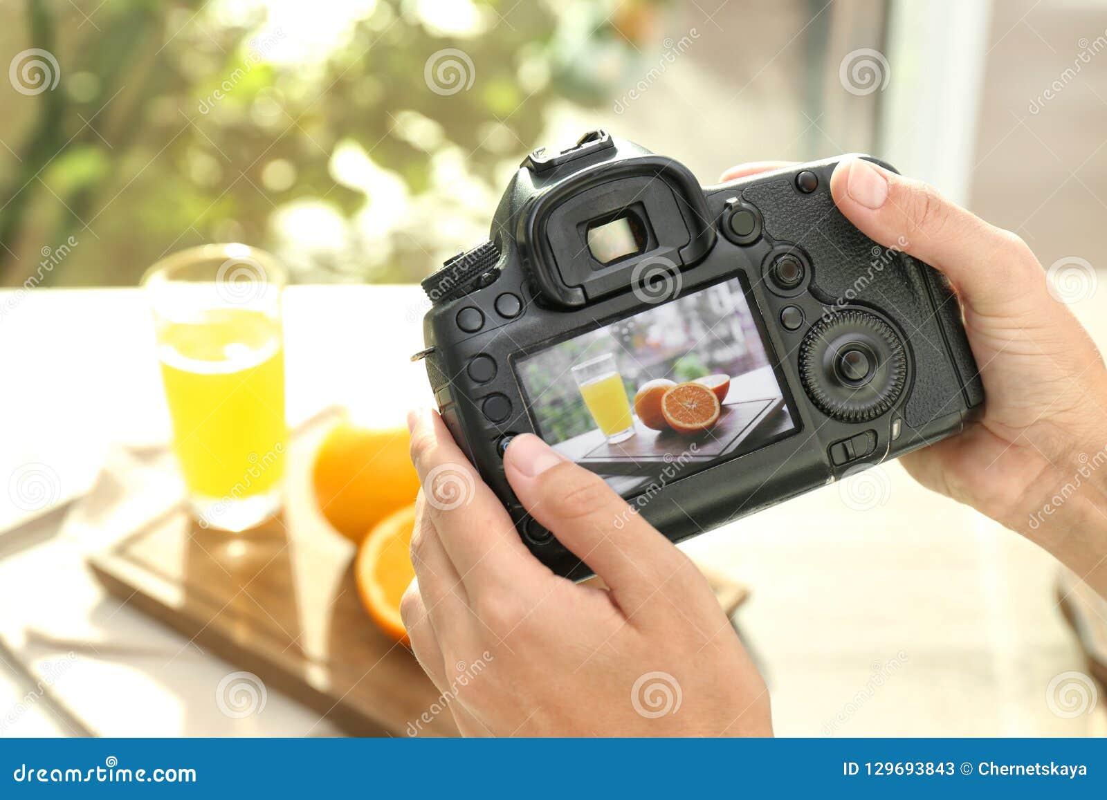 Vrouwelijke fotograaf die beeld van sap en sinaasappelen met professionele camera nemen