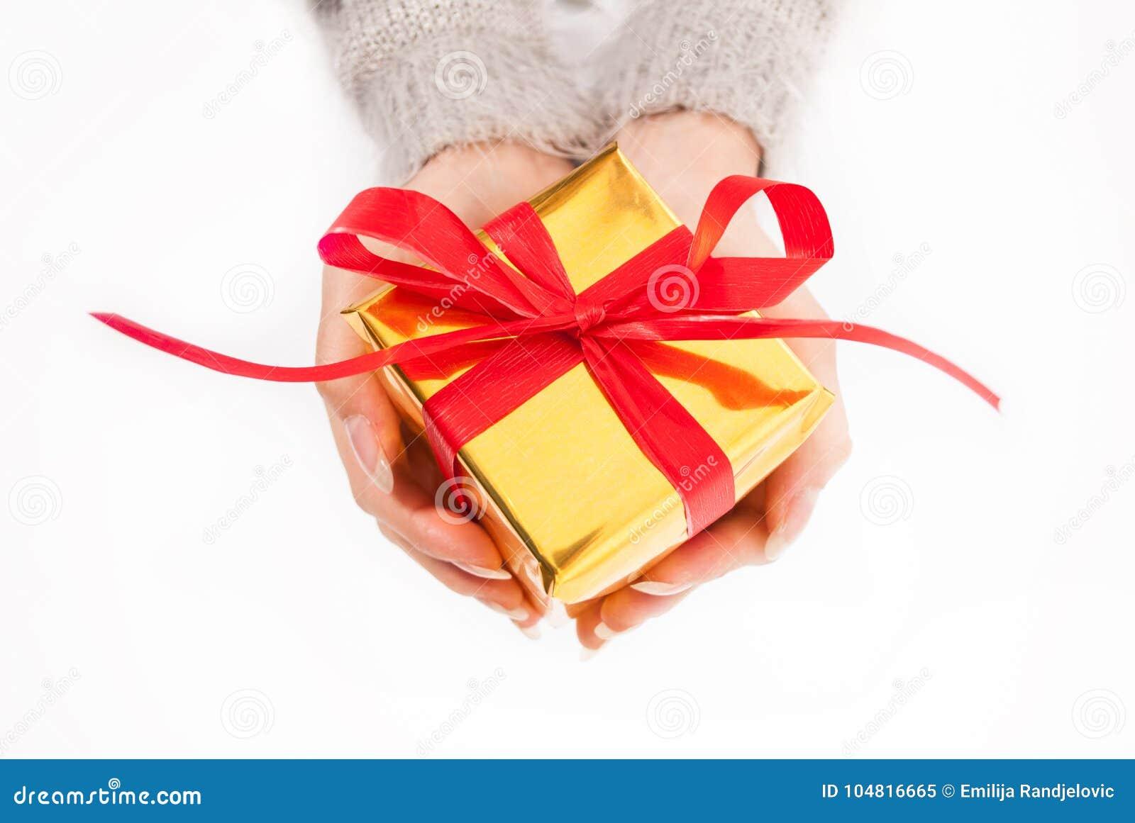 Vrouwelijke hand die gouden doos houden met rode boog op witte achtergrond huidig