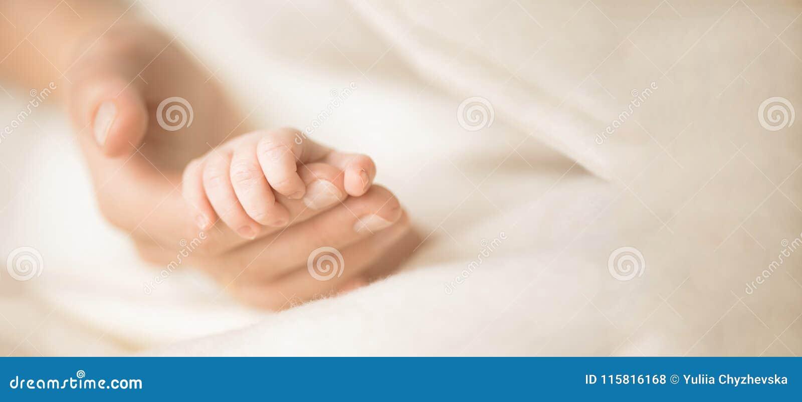 Vrouwelijke hand die haar pasgeboren baby` s hand houdt Mamma met haar kind Moederschap, familie, geboorteconcept Exemplaarruimte